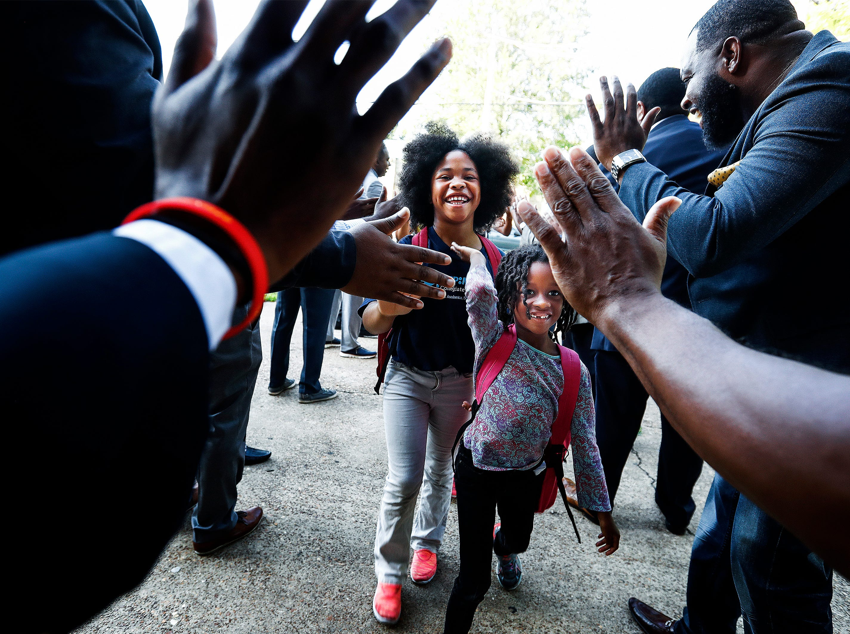 KIPP Memphis Collegiate Elementary students Lisa Taylor, 9, (left) and Lauren Walker, 5, (right) are greeted by members of the Men's Morning Huddle, as they get high fives after arriving for the first day of school. Throughout the year, the group that brings men together to set a positive example for children, will ascend on area schools to help motivate students.