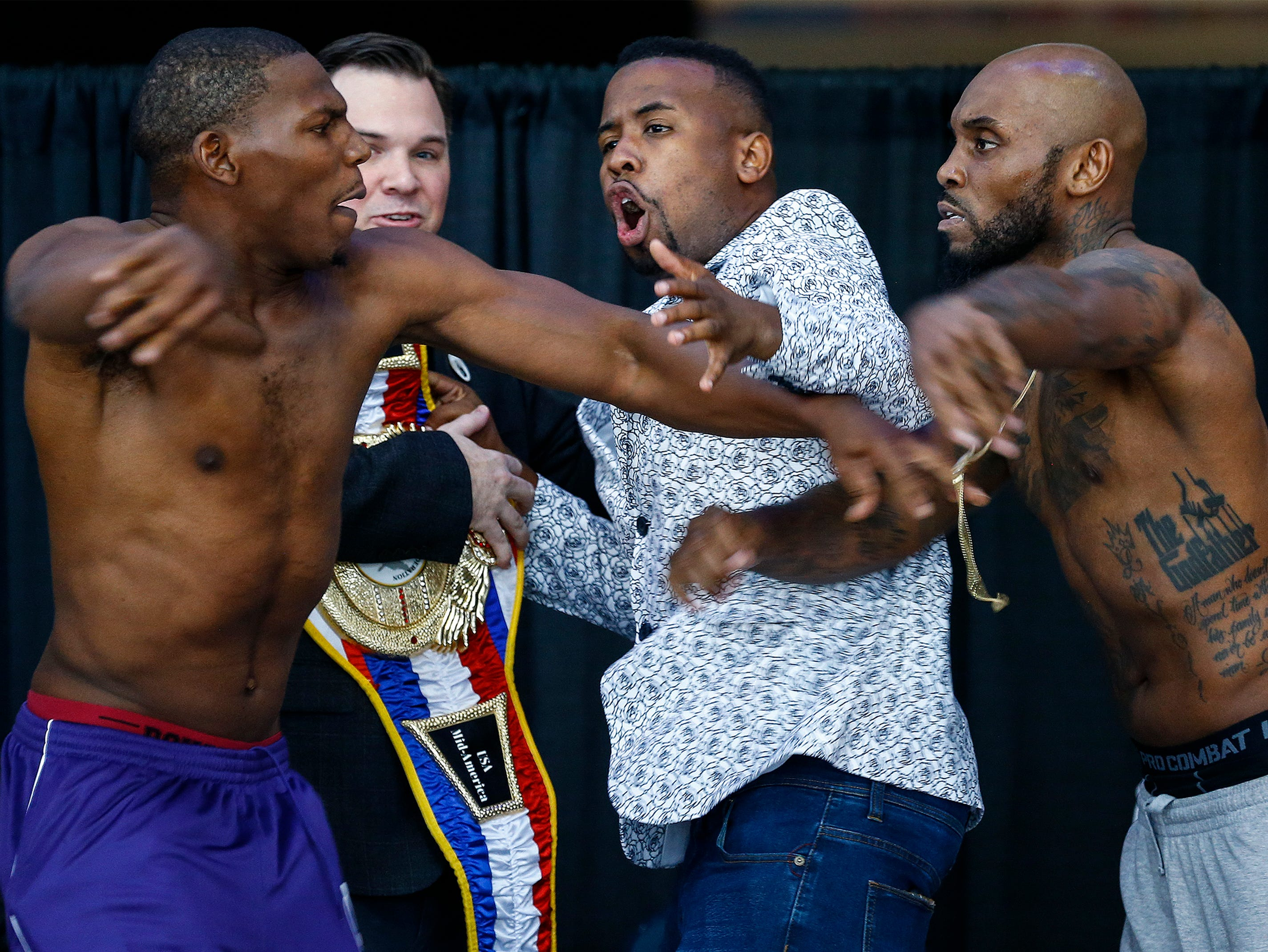"""Promoter Lank the King (middle) tries to hold back boxers Lamar Harris (left) and Lanell Bellows (right) after they get into an altercation while facing-off during weigh-ins for their bout on the """"Big Payback Championship Boxing FightÓ at the FedExFourm."""