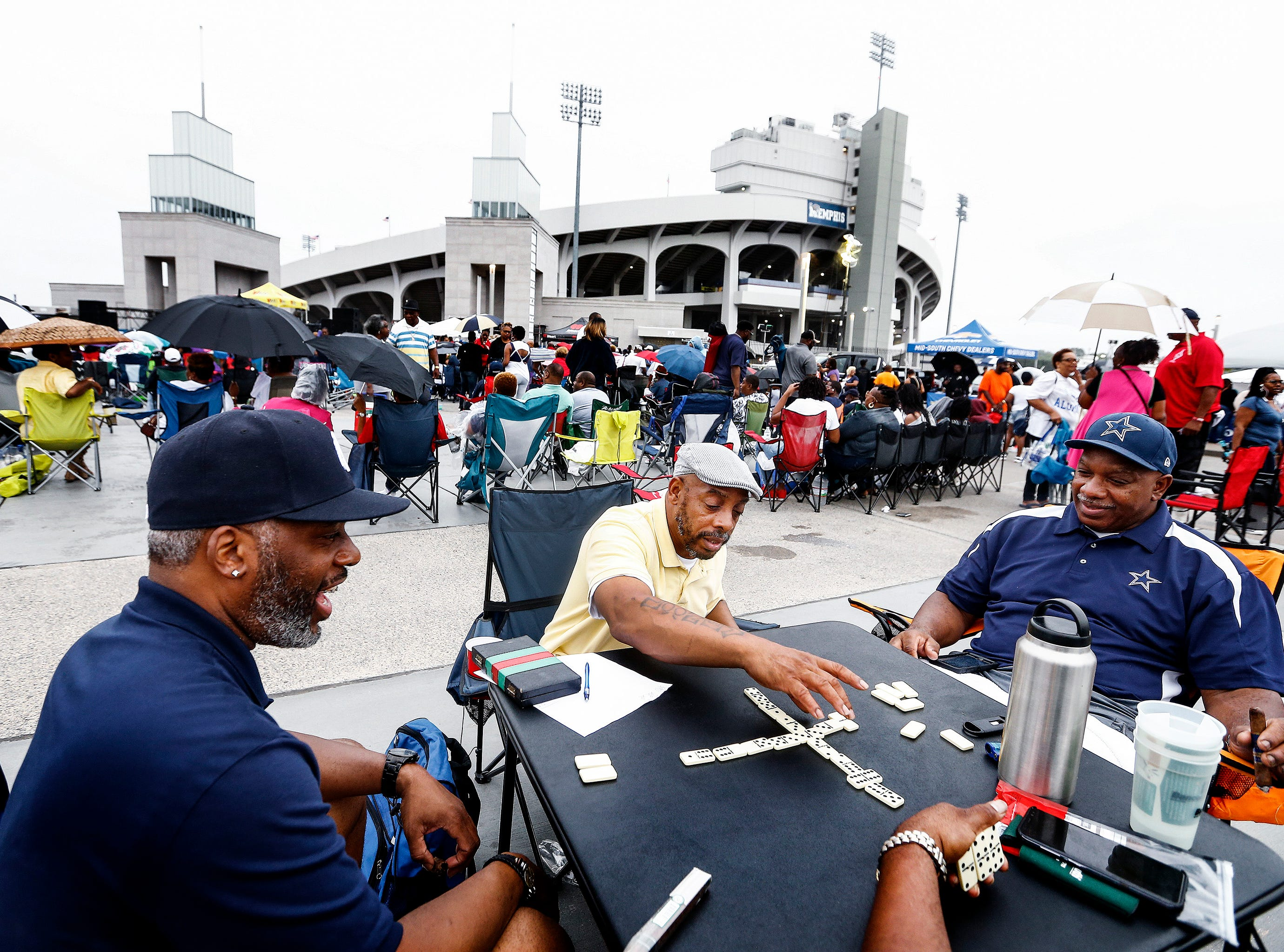 Friends (left to right) Melvin Hill, Lonnie Williams, and twin brother Johnnie Willians play a round of dominos, as they enjoy themselves during the Tom Joyner Morning Show, as they celebrate the 2018 Southern Heritage Classic at The Liberty Bowl Memorial Stadium, Friday morning.