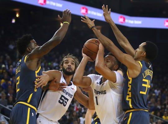 Memphis Grizzlies' Kyle Anderson (1) shoots beside Joakim Noah (55) as Golden State Warriors' Jordan Bell, left, and Shaun Livingston, right, defend in the first half of an NBA basketball game Monday, Dec. 17, 2018, in Oakland, Calif. (AP Photo/Ben Margot)