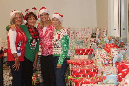 Volunteers Colleen Bowler, Jayne Hampton, Kim Bappe and Sue Thomas are seen with part of the treasure trove of presents given out during the evening.