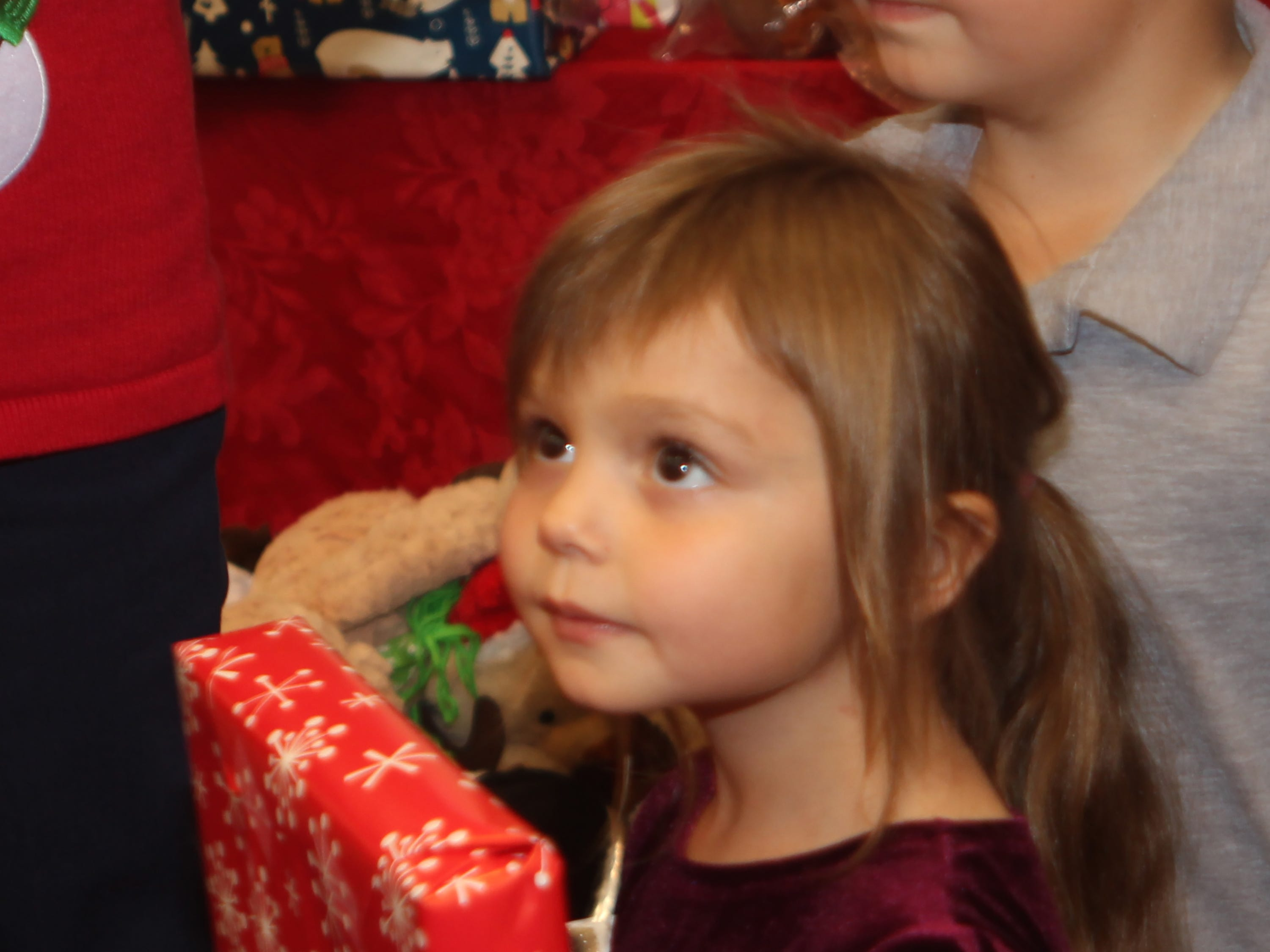 Kairi Camandona gazes up at Santa in typical wonderment after receiving her gift at the Y's Giving Tree event.