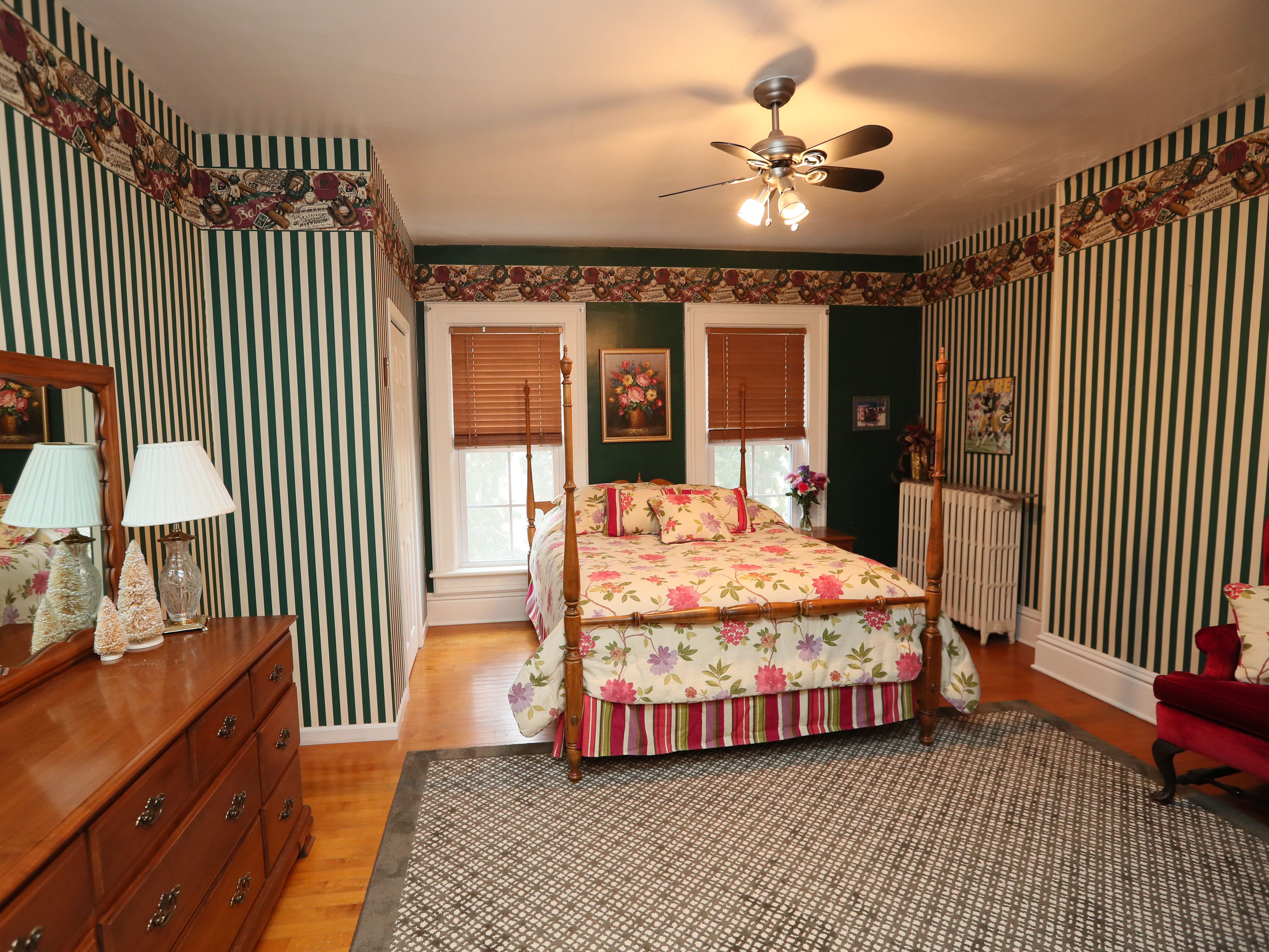 "This guest bedroom features a four-poster bed and striped wallpaper. Dionne Kelm describes their decorating style as eclectic, not trendy but made up of ""what we love."""
