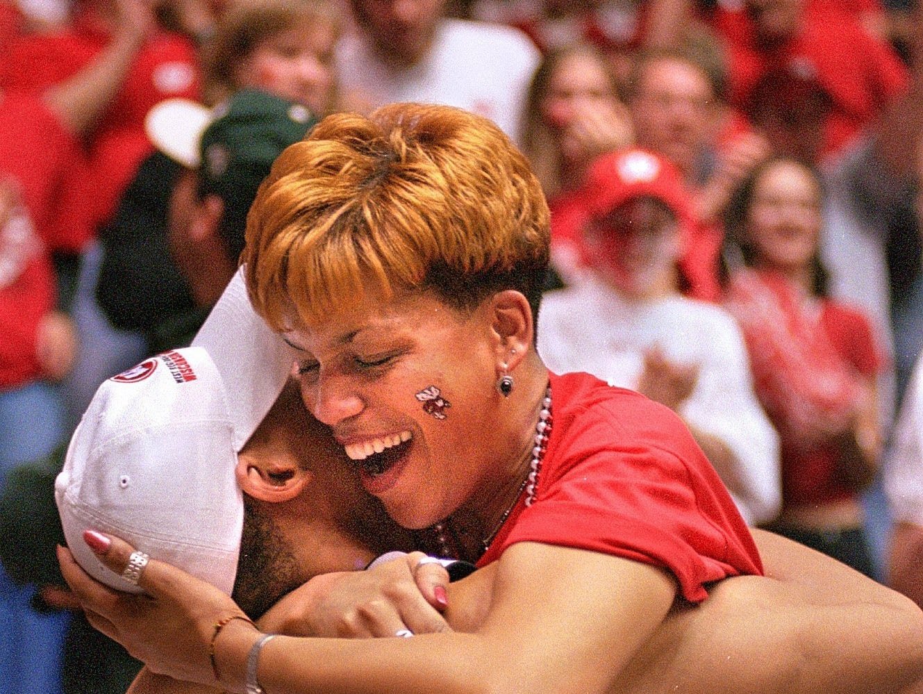 Wisconsin's Maurice Linton hugs his mother, Cynthia, in the stands to celebrate Wisconsin's victory over Purdue.