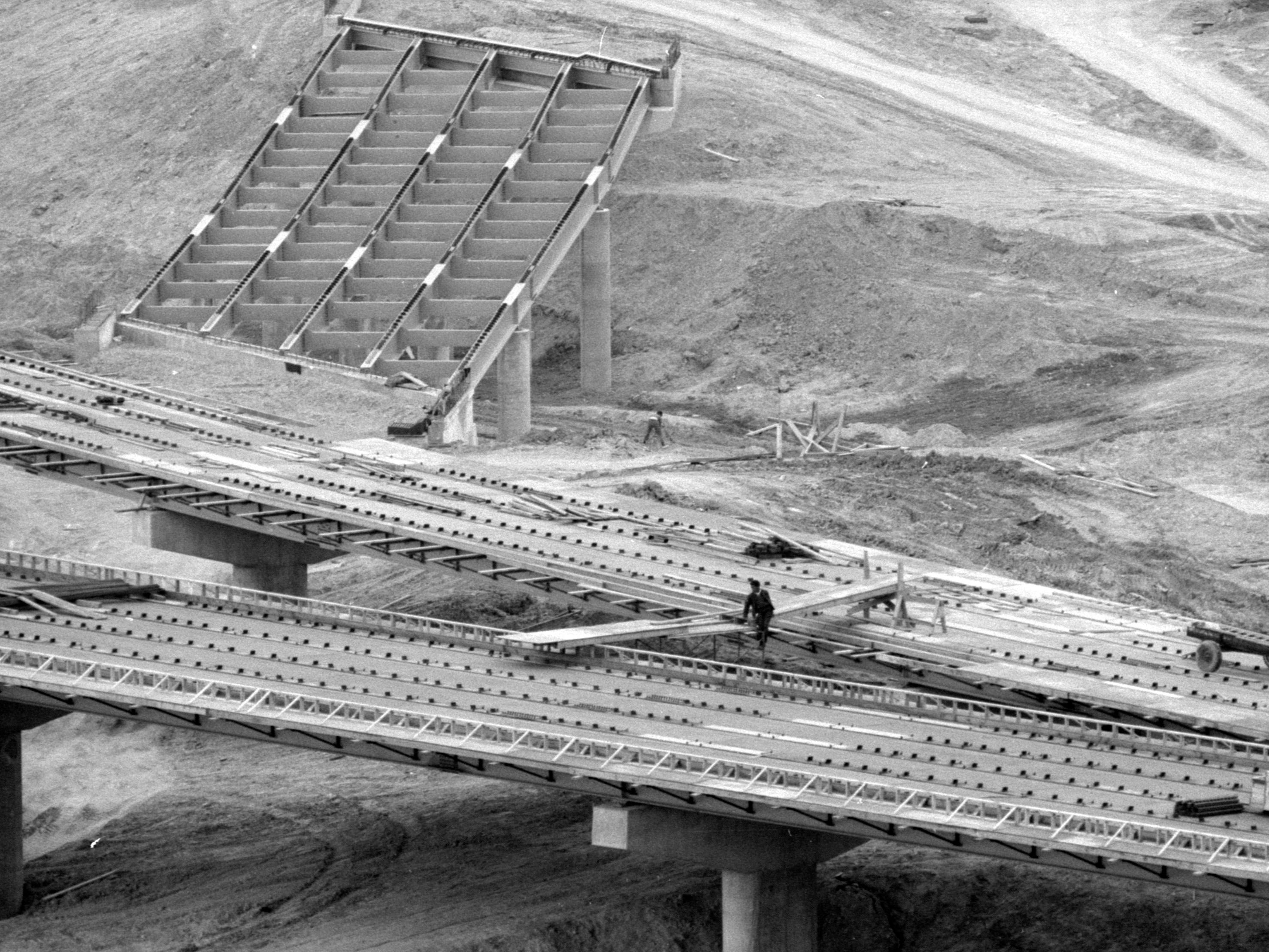 A construction worker crosses a still-under-construction on-ramp at the Central Interchange during construction in the spring of 1968. The project was renamed the Marquette Interchange later that fall.
