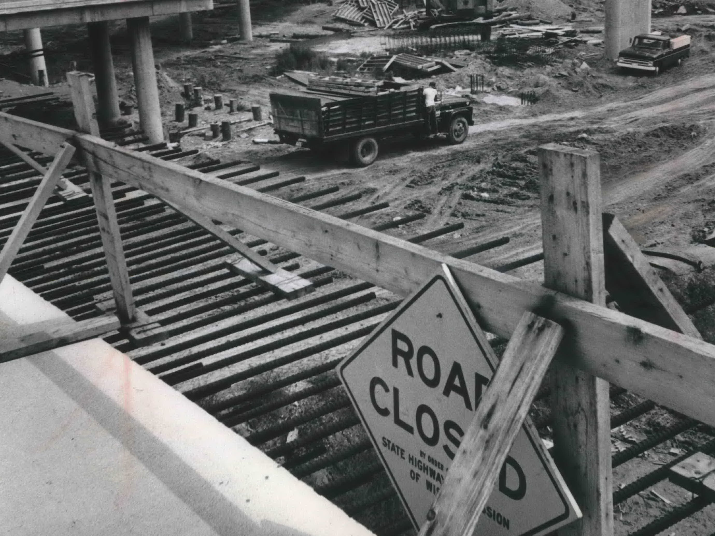 A highway sign, possibly posted as a prank, decorates a barricade blocking the end of one of the still-under-construction ramps to the Central Interchange in downtown Milwaukee.  This photo was published in the Aug. 5, 1965, Milwaukee Journal.