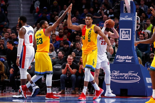 Giannis Antetokounmpo of the Bucks is congratulated by teammate Sterling Brown after making a basket while getting fouled late in the game against the Pistons.