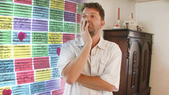 Steve Burrows stands in the dining room of his Los Angles home, in front of notes concerning his mother's medical condition and the family's legal battle.