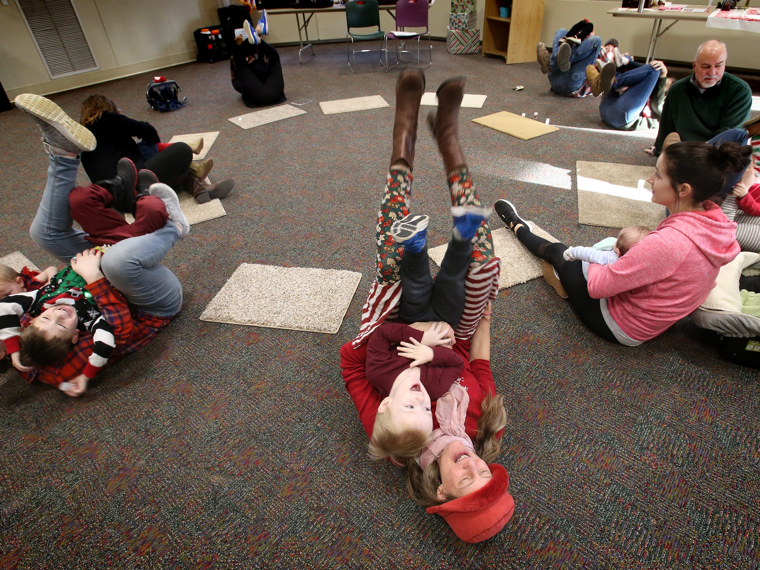 """Fifiteen chilren and adults invert while moving to the rhyme """"Humpty Dumpty"""" during Miss Julie's Music Fun Christmas Music Party at the Germantown Community Library on Dec. 18."""