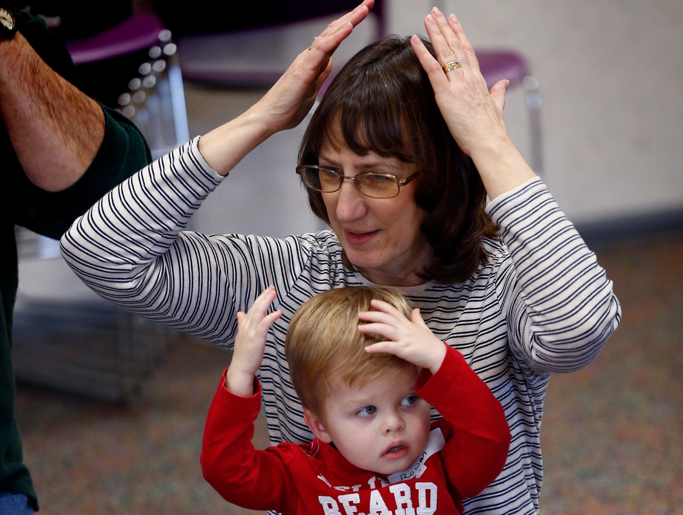 Rowan and Greta Williams match the motions of a song during Miss Julie's Music Fun Christmas Music Party at the Germantown Community Library on Dec. 18.