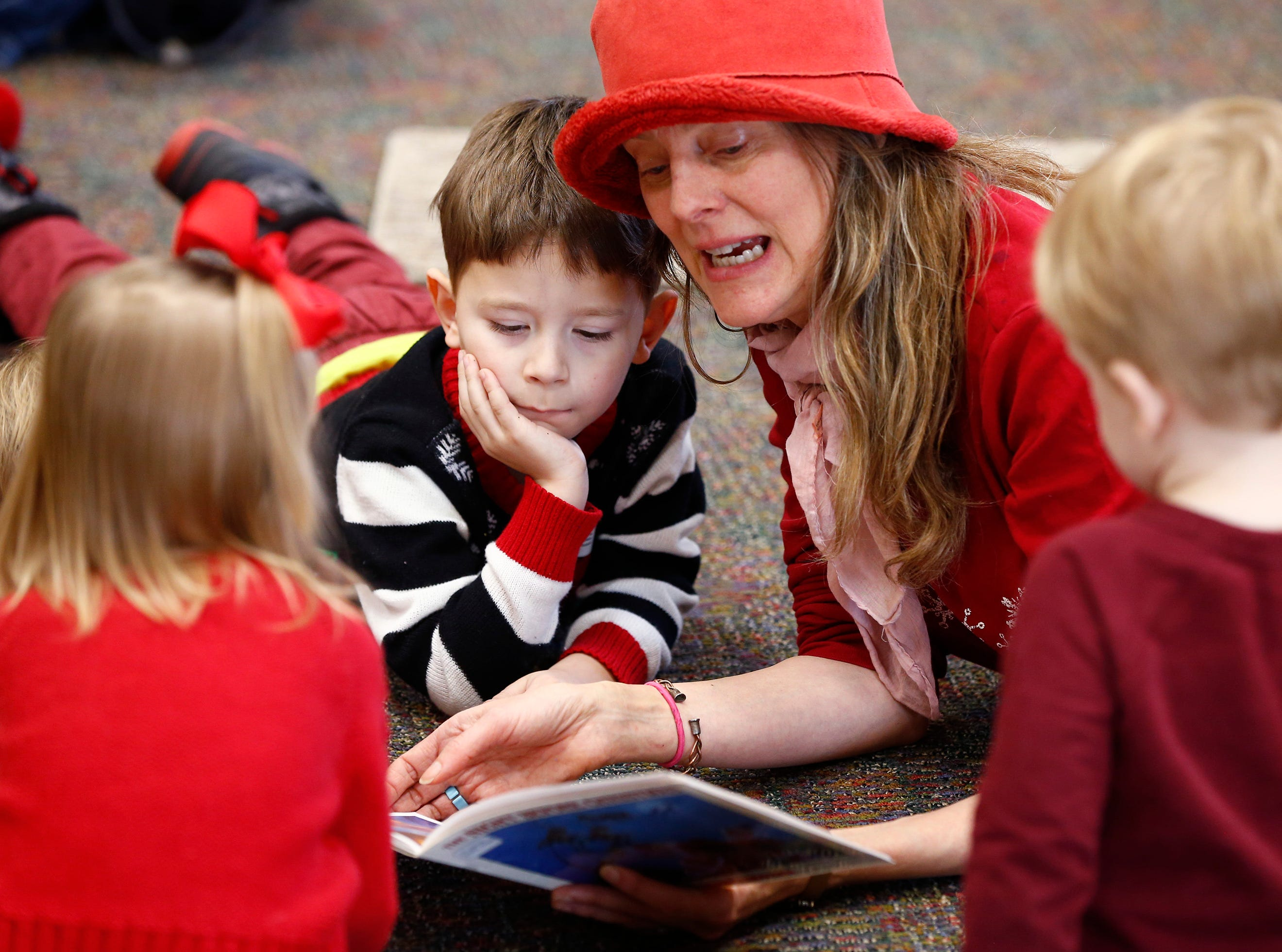 """Julie Thompson reads """"Twas the Night Before Christmas"""" in a tummy circle during Miss Julie's Music Fun Christmas Music Party at the Germantown Community Library on Dec. 18."""