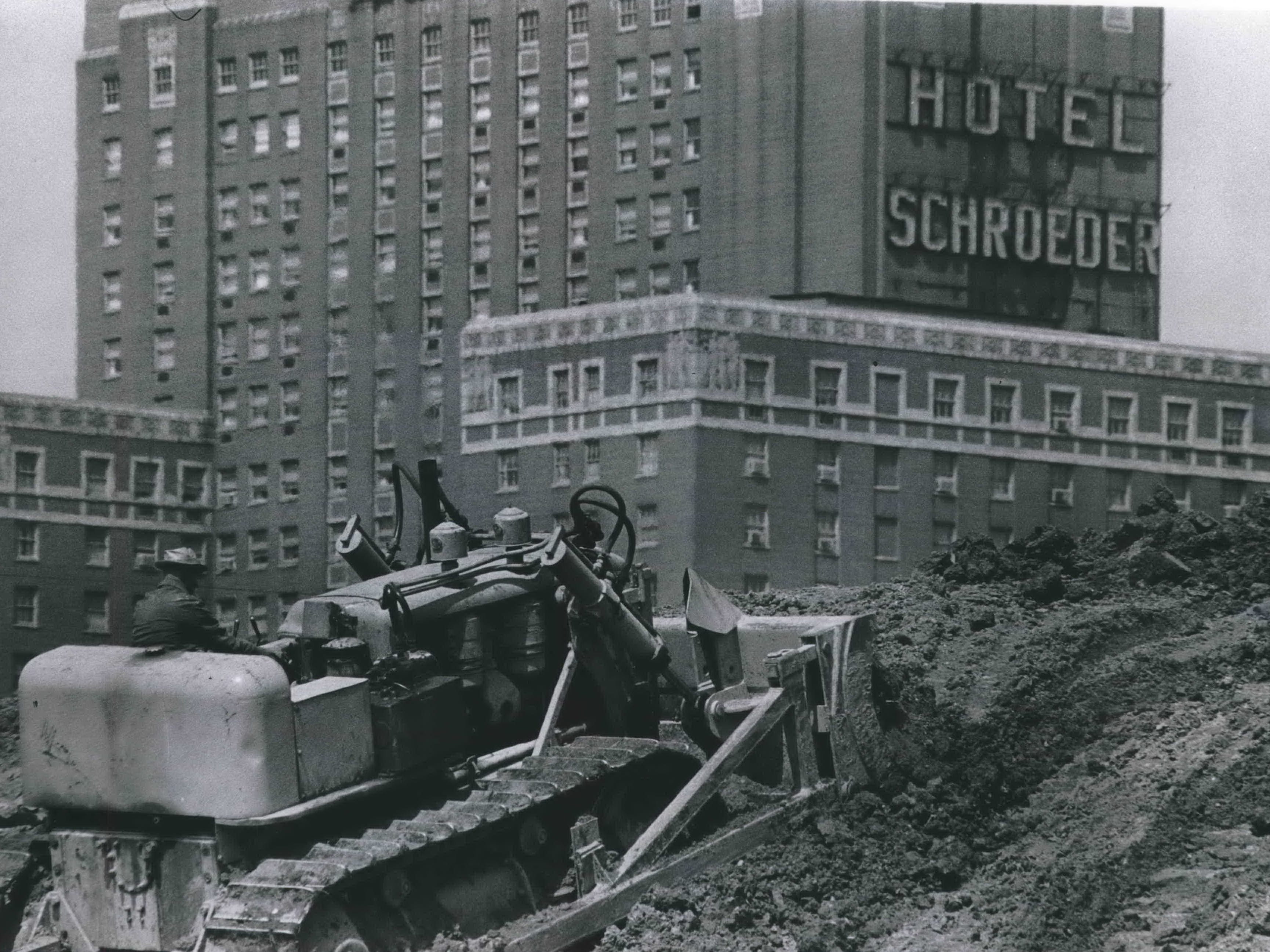 A bulldozer pushed dirt at N. Eighth Street and W. St. Paul Avenue, clearing the way for the southern end of the Central Interchange in downtown Milwaukee. The scene was distorted by using a telephoto lens, which makes the Hotel Schroeder (now the Milwaukee Hilton City Center, 509 W. Wisconsin Ave.) appear closer than it really was. This photo was published in the June 4, 1964, Milwaukee Journal.
