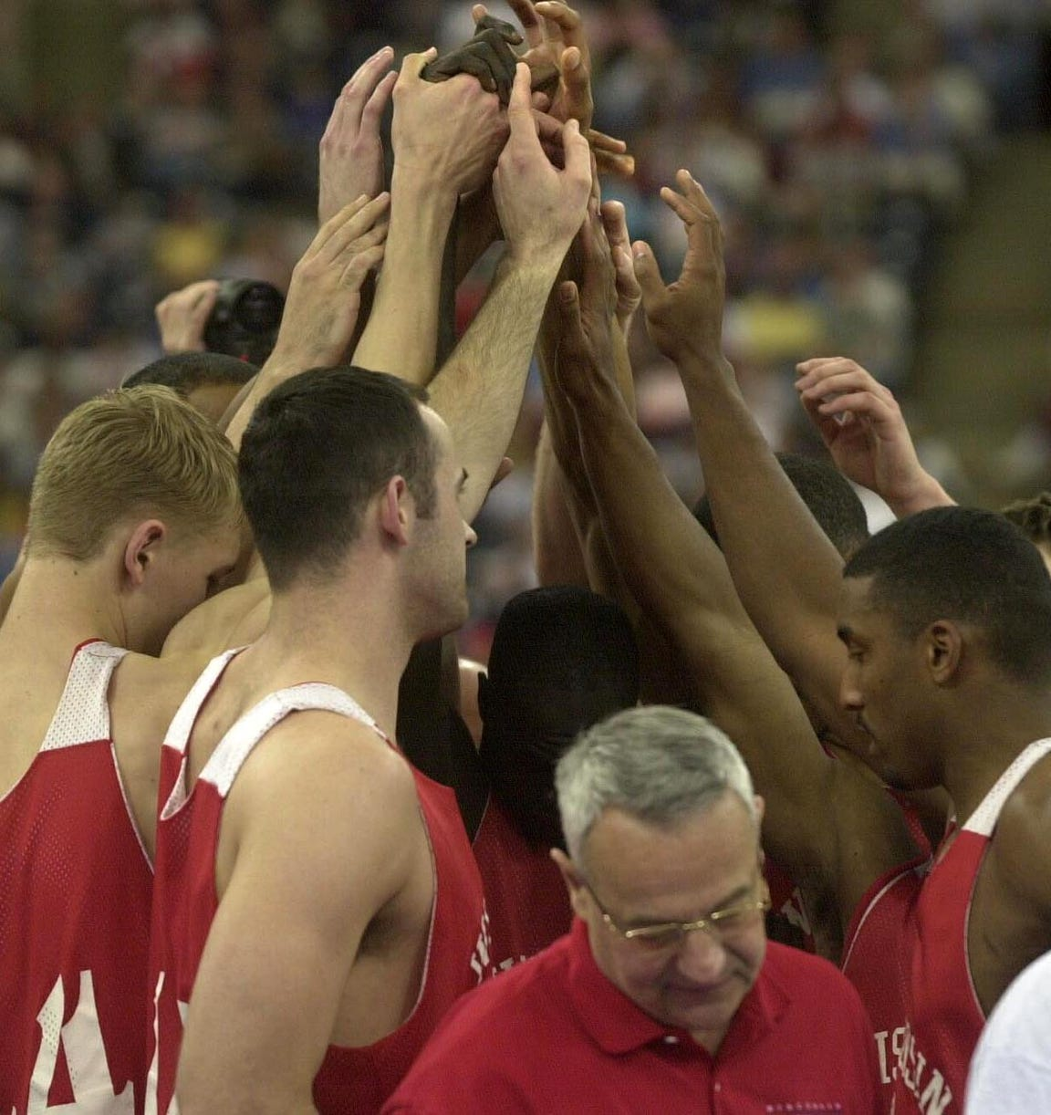Dick Bennett leaves the huddle as the players unite with raised hands clenched together after their practice ended at the RCA Dome during the 2000 Final Four.