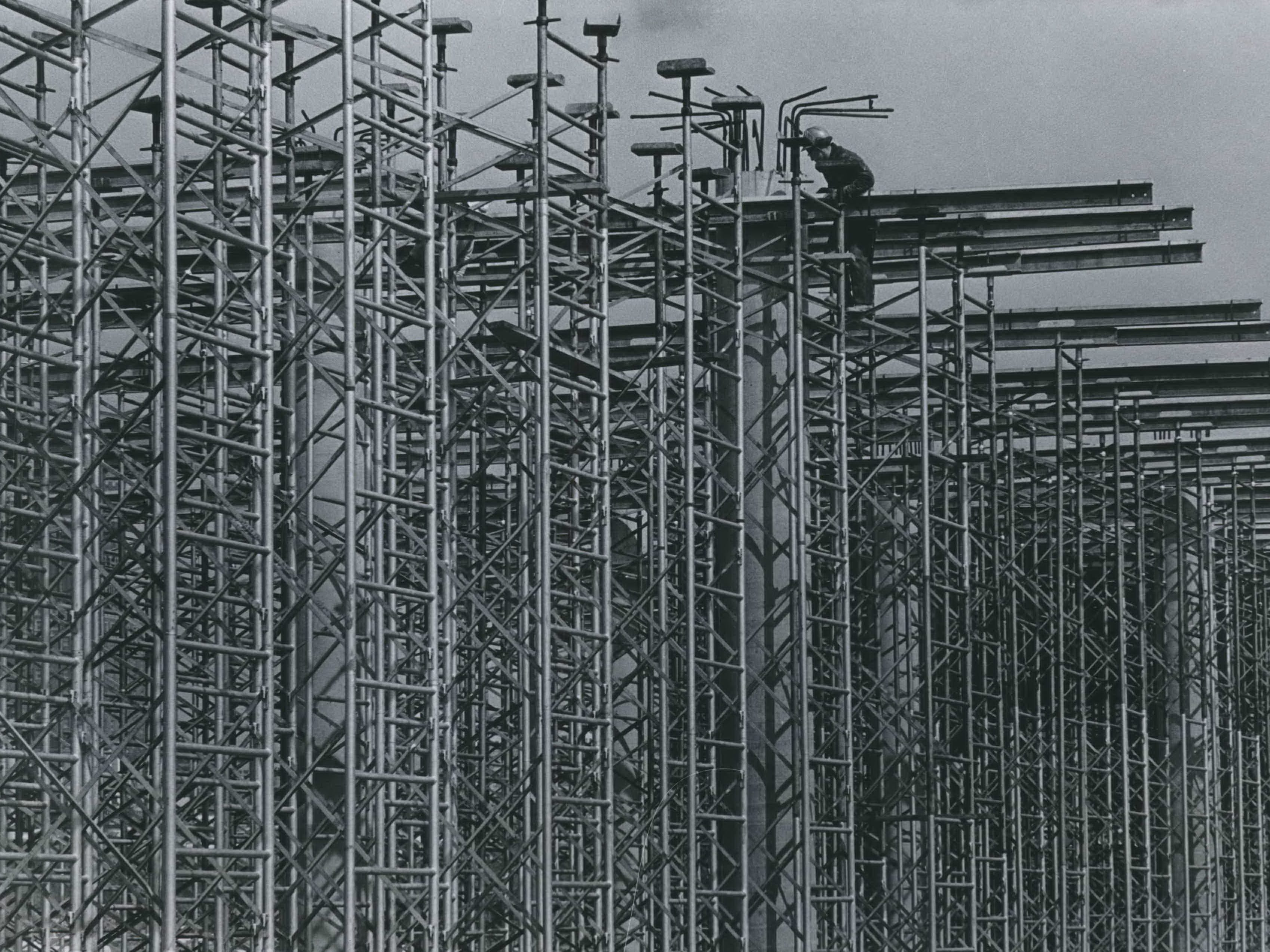 Scaffolding is being pieced together like a giant Erector set at the site of the Central Interchange in downtown Milwaukee. The scaffolding was to support forms for a future concrete roadway that will carry traffic high above the ground. This photo was published in the April 1, 1965, Milwaukee Journal.