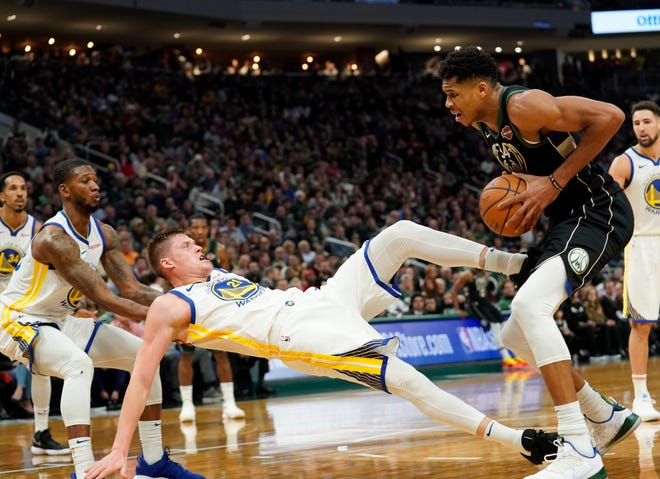 Giannis Antetokounmpo is called for a charge on Golden State's Jonas Jerebko.