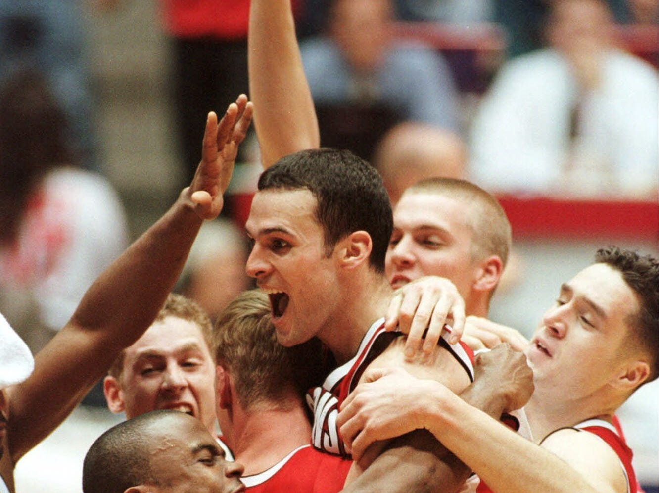 Wisconsin's Mike Kelley, center, celebrates with teammates after beating Purdue 64-60 in the NCAA West finals Saturday, March 25, 2000.