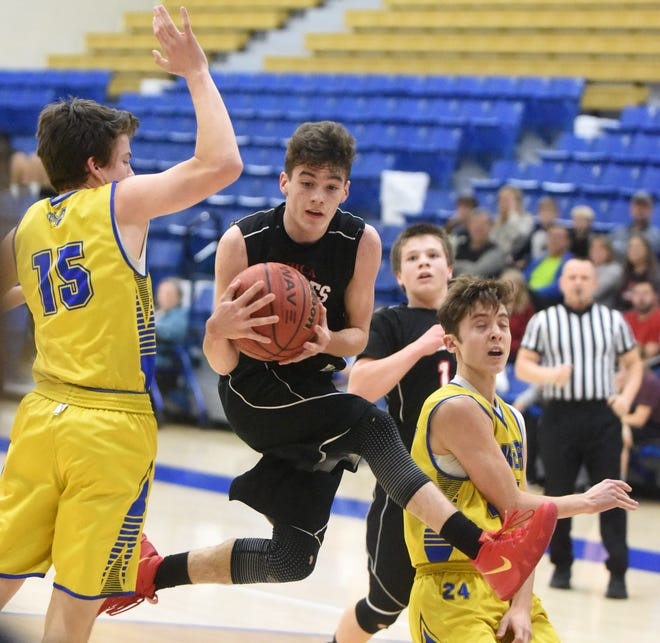 Mountain Home Christian Academy's Trenton Cox grabs a rebound between Bombers Jake McGehee and Luke Hinson on Monday night at The Hangar.