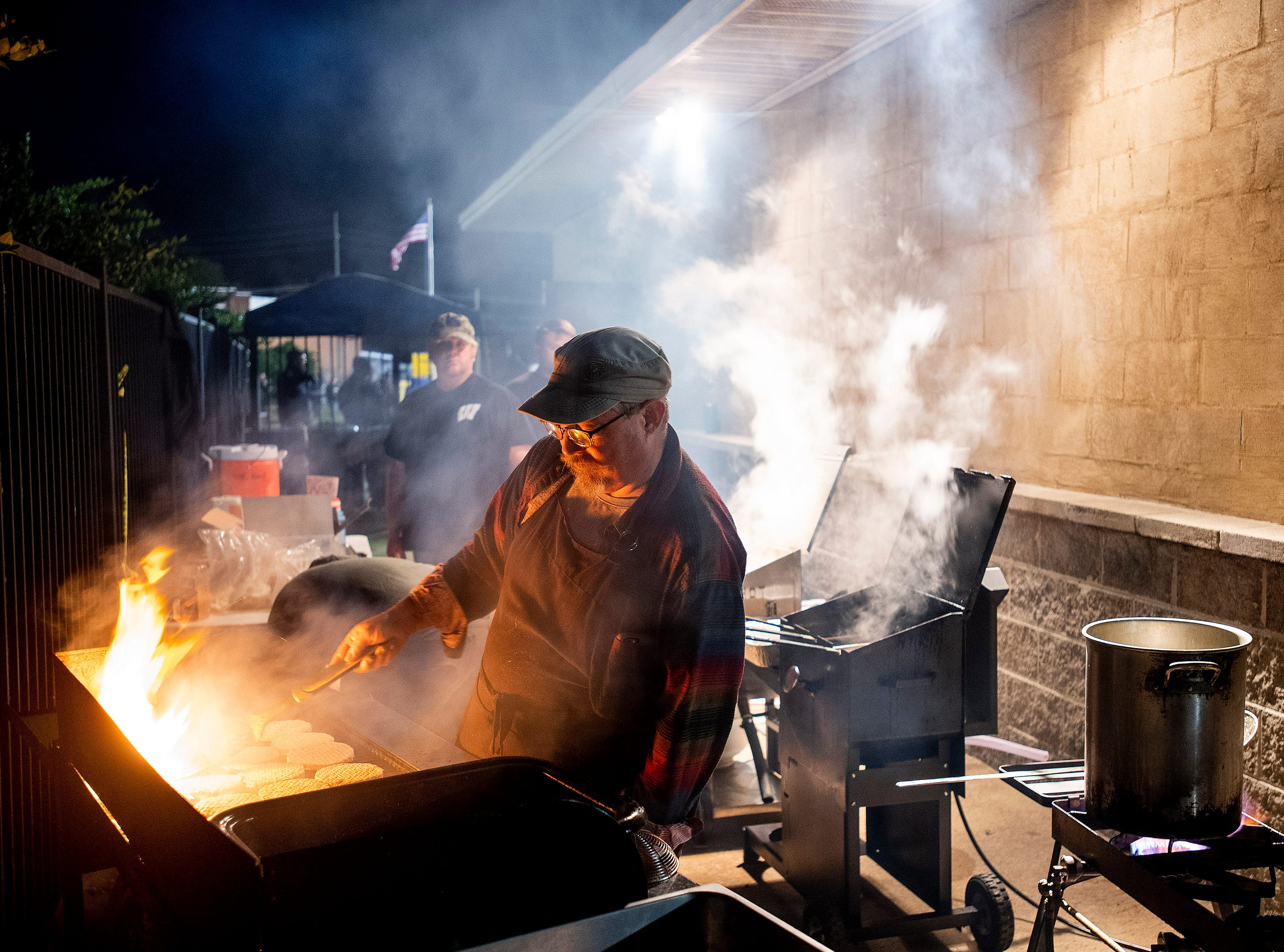 Grilling hamburgers for the concession stand at the Wetumpka vs. Daphne game at Hohenburg Field in Wetumpka, Ala., on Friday November 9, 2018.