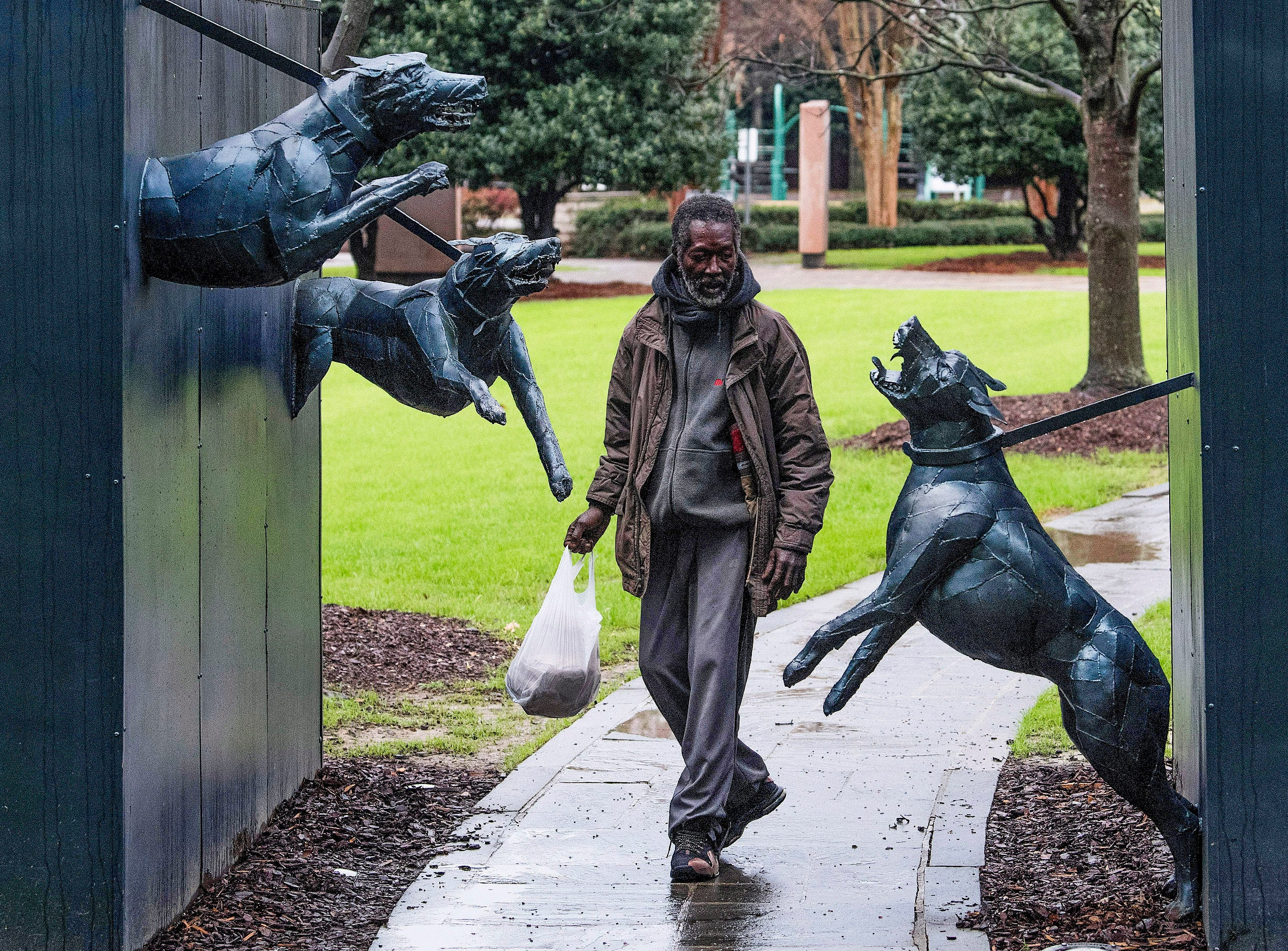 Joe, who likes to hang out in historic Kelly Ingram Park in Birmingham, Ala., and point out the civil rights statues for tips, walks through the police dog statue on Thursday March 1, 2018.