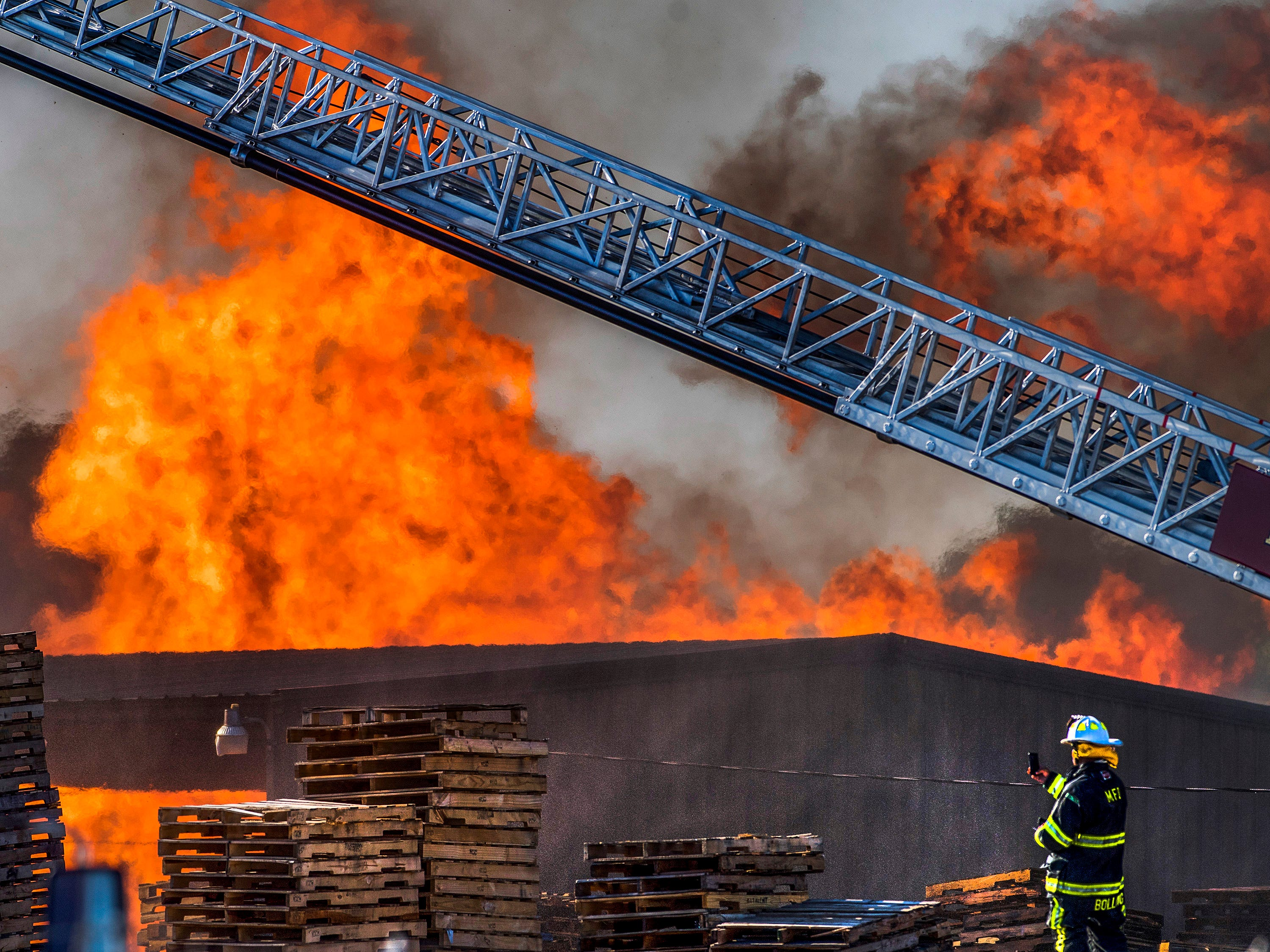 A Montgomery Fire Fighter snaps a photo with his phone as firefighters fight a pallet warehouse fire off of Furnace Street in North Montgomery, Ala. on Wednesday April 18, 2018.