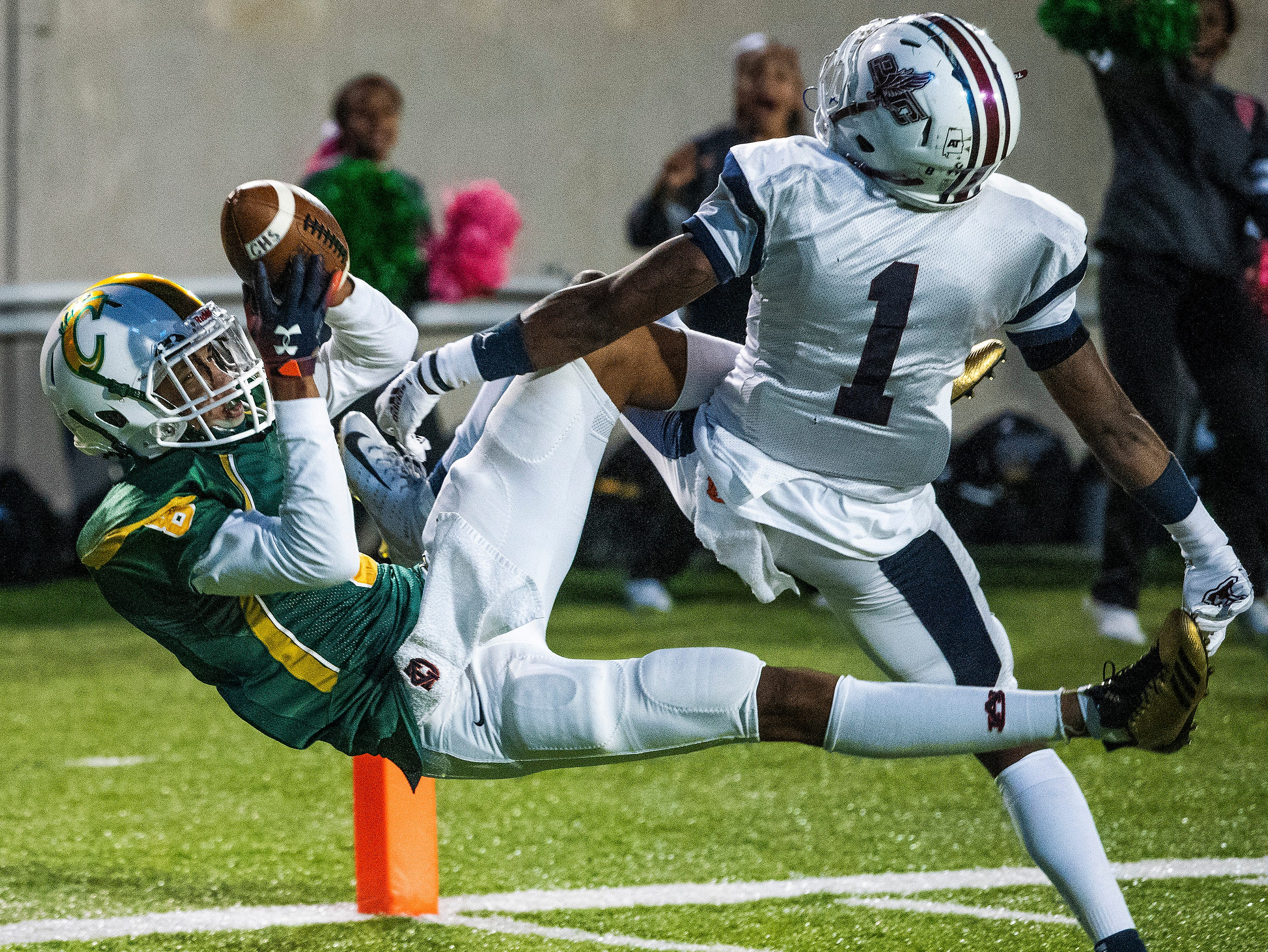 Carver's Ethan Stinson (8) loses control of the ball as he falls into the engine on an incomplete pass while defended by Park Crossing's Jaden Taylor at Cramton Bowl in Montgomery, Ala., on Friday October 26, 2018.