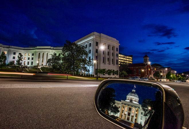The state capitol building is seen in a rear view mirror on Dexter Avenue.