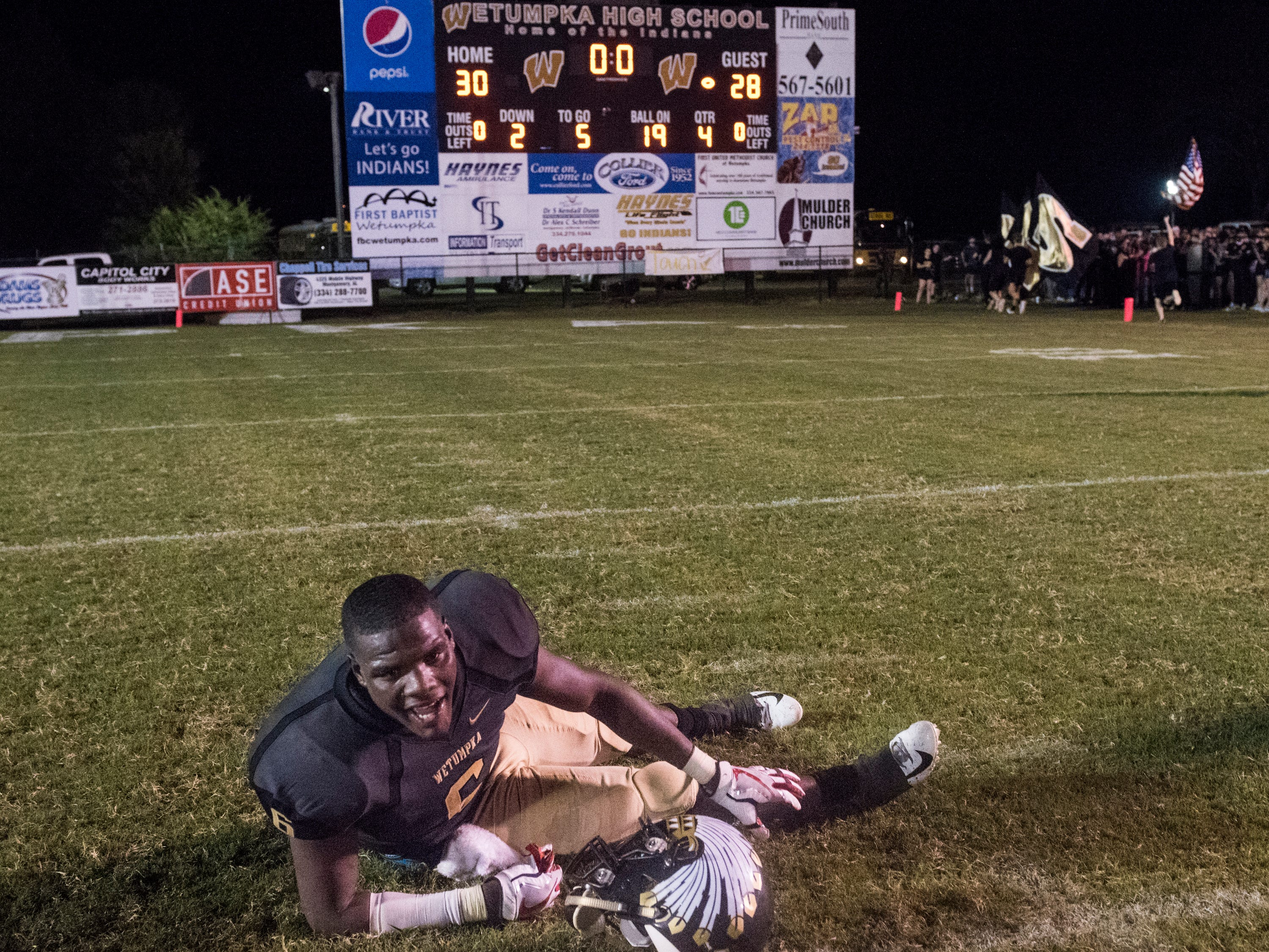 Wetumpka's quarterback TyQuan Rawls (6) goes down with a cramp after celebrating and leading his team to victory against Opelika at Hohenberg Field in Wetumpka, Ala., on Friday, Sept. 14, 2018. Wetumpka defeated Opelika 30-28.