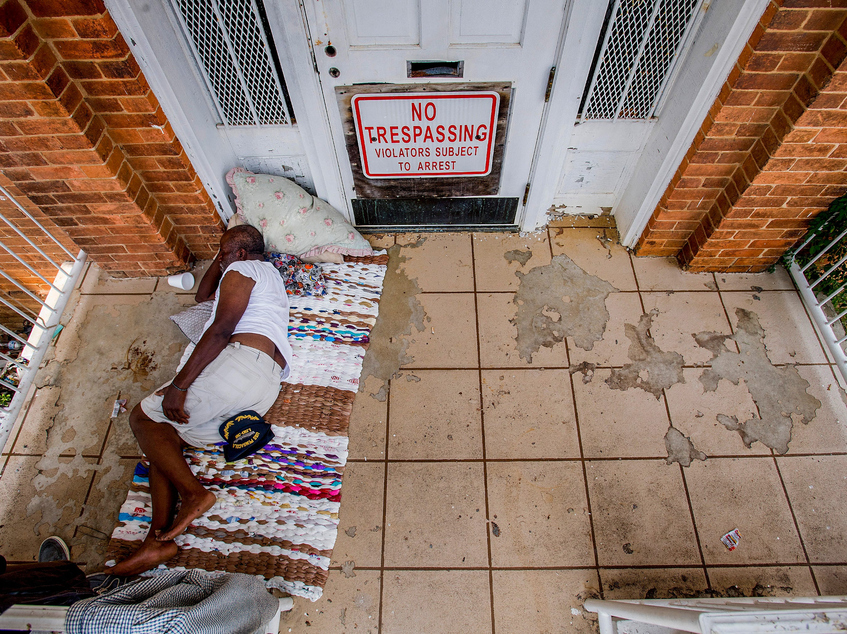 Willie Love takes a nap on the porch of the Chappell House on Maxwell Blvd in Montgomery, Ala., on Thursday July 19, 2018. Several people are sleeping on the porches of the historic home near the Salvation Army shelter.