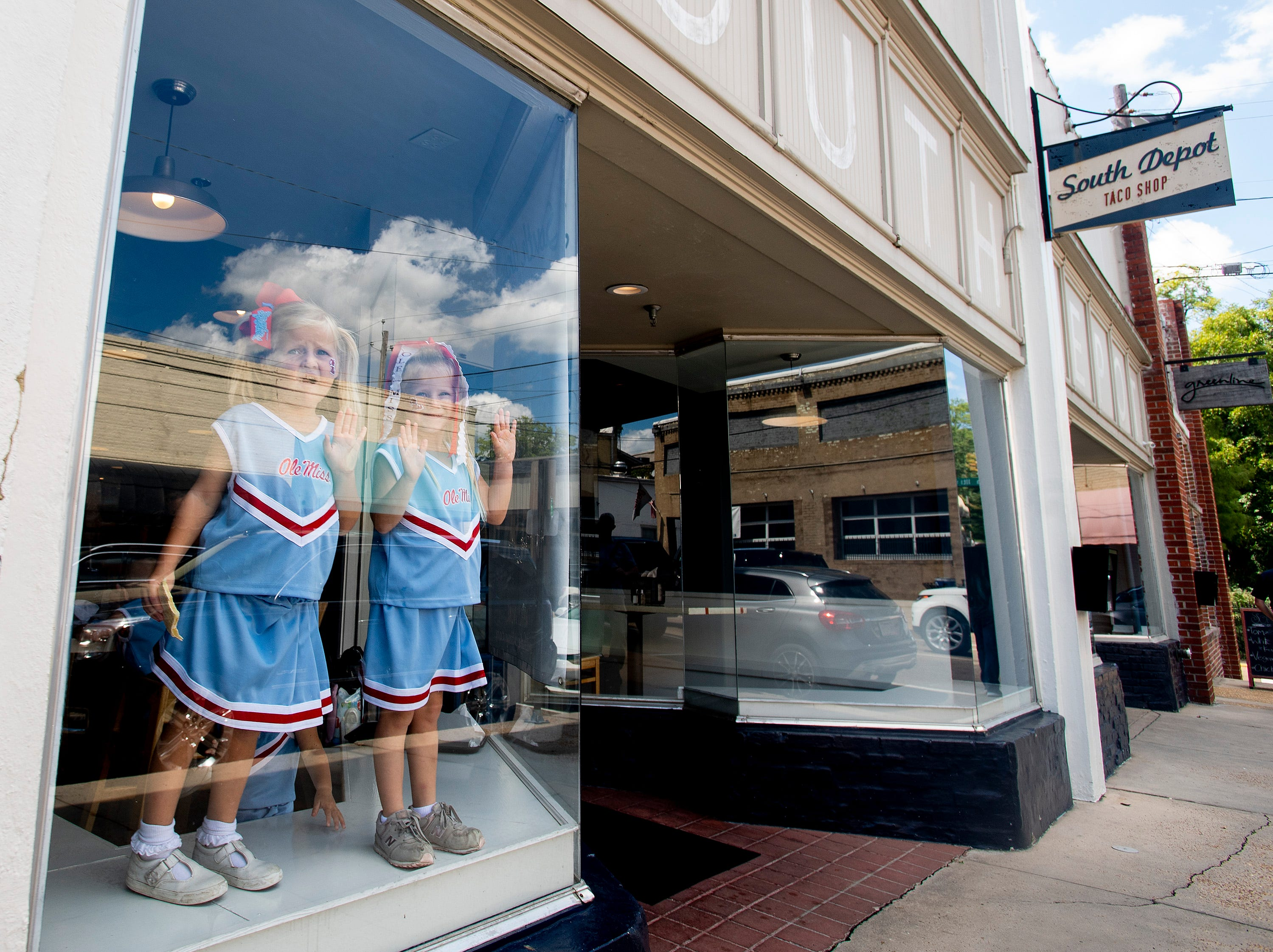 Young Ole Miss fans dressed as cheerleaders stand in a restaurant window in Oxford, Ms., before the Ole Miss vs. Alabama game on Saturday September 15, 2018.