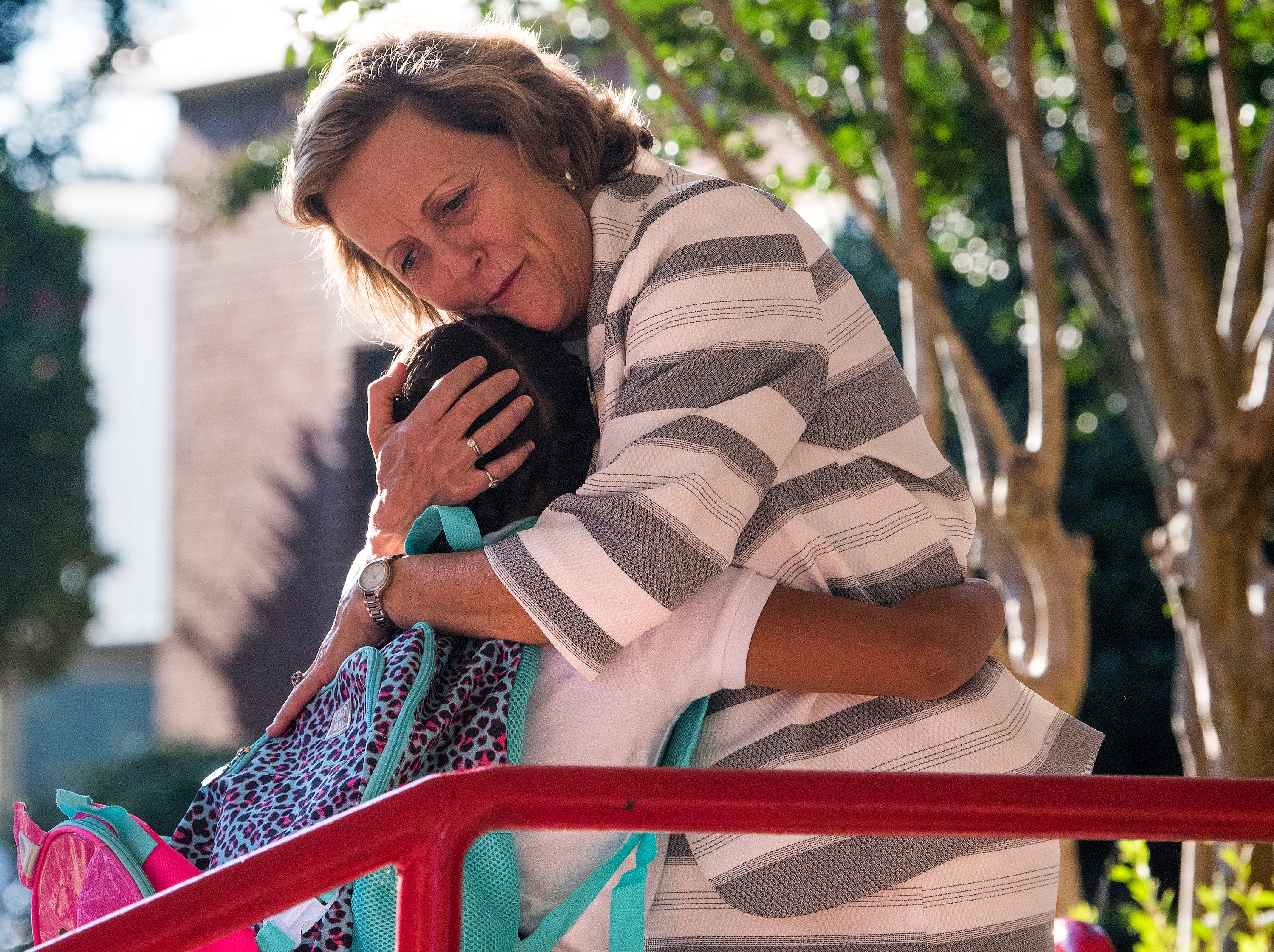 Flowers Elementary School principal Ethel Barnes hugs students as they arrive for the first day of classes at Montgomery Public Schools in Montgomery, Ala., on Monday, August 6, 2018.