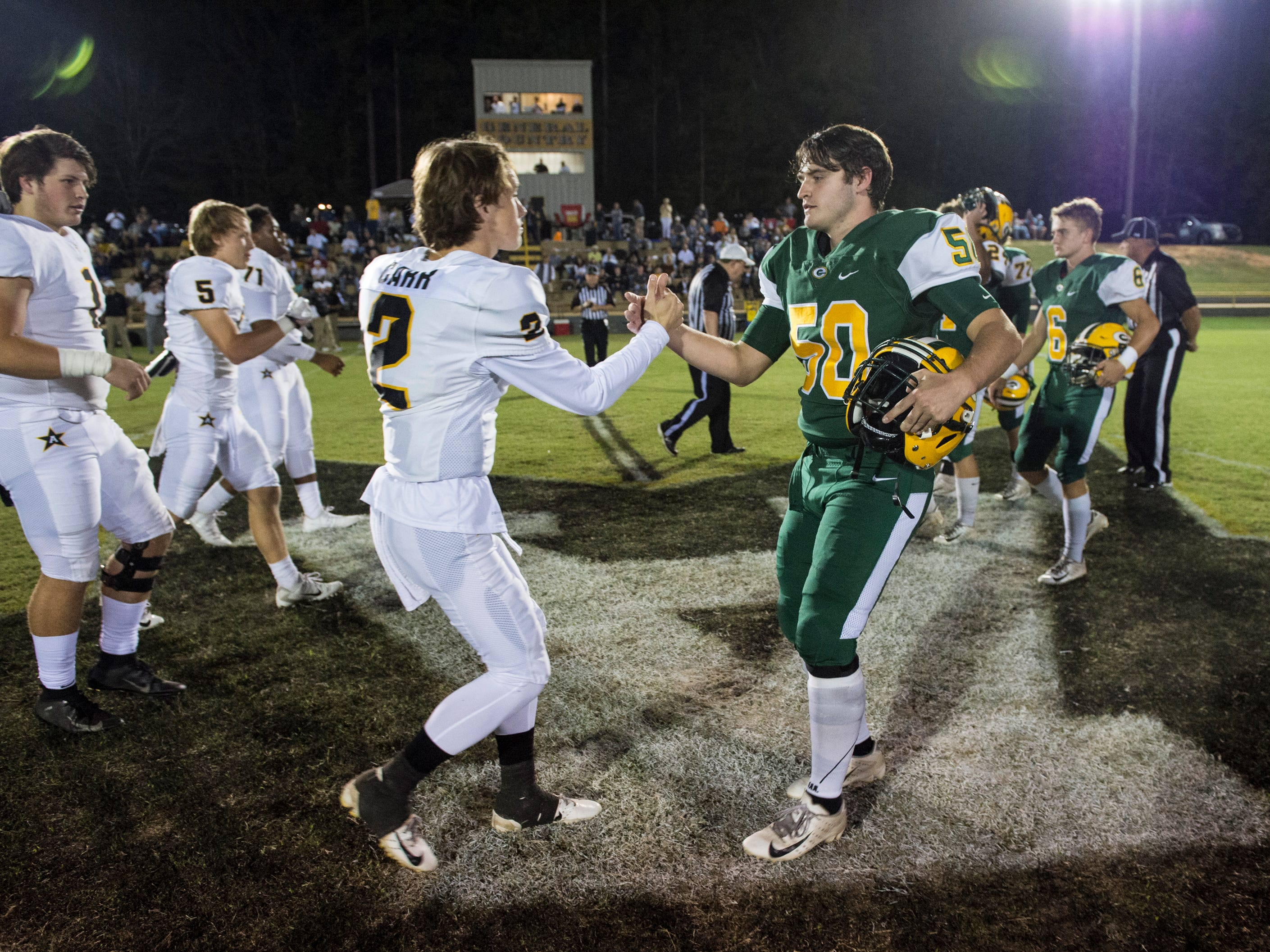 Team captains from Edgewood and Autauga shake hands at midfield after the coin toss at Autauga Academy in Prattville, Ala., on Thursday, Oct. 18, 2018.