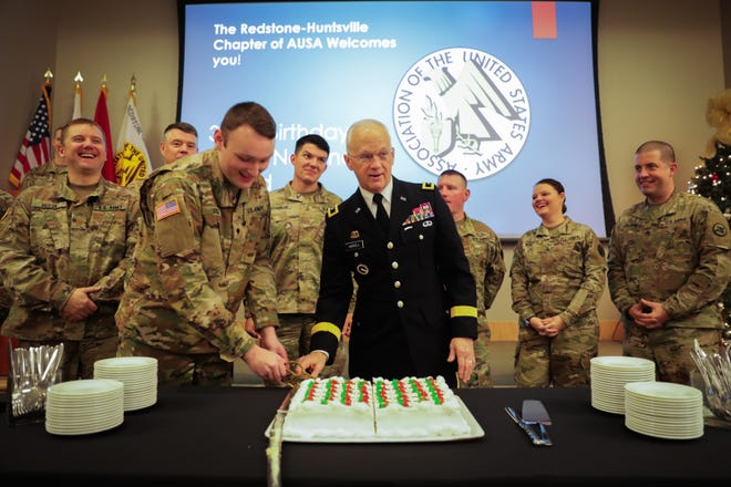 Spc. Michael Izzo, an intelligence analyst with Higher Headquarters Detachment, 203rd Military Police Battalion, Army National Guard, cuts the birthday cake with Maj. Gen. Allen Harrell, assistant deputy commanding general for National Guard Affairs, Army Materiel Command, during the Army National Guard's 382nd birthday, hosted by the Redstone-Huntsville Chapter of the Association of the U.S. Army at the Jackson Center in Huntsville. Traditionally, the oldest member in attendance is joined by the youngest to cut the cake.