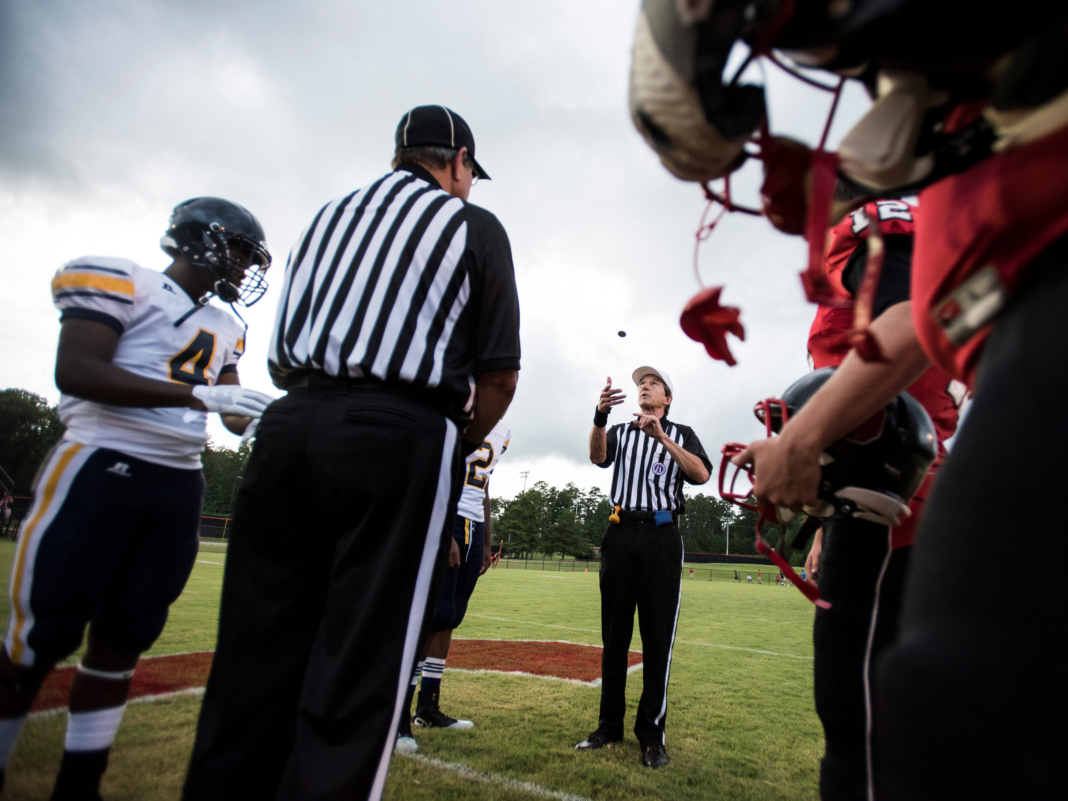 Team captains join the officials at midfield for the coin toss as Success Unlimited Academy takes on Springwood in the schools first every football game at Springwood High School in Lanett, Ala., on Friday, Aug. 17, 2018. Springwood defeated Success Unlimited Academy 23-12.