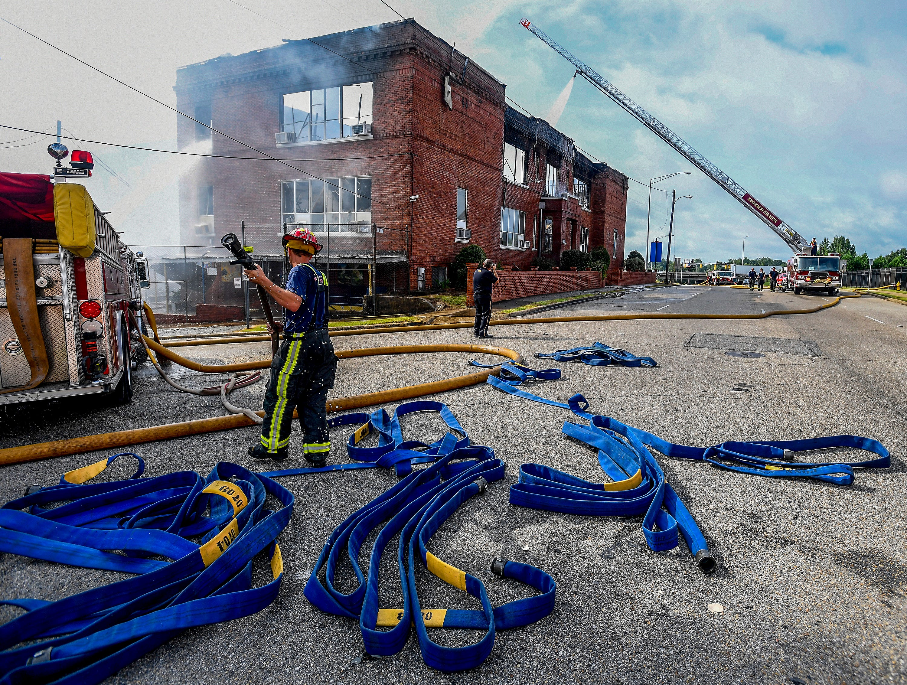 Montgomery firefighters work the scene of a major fire at Booker T. Washington Magnet School campus in Montgomery, Ala. on Saturday morning August 18, 2018. A building was destroyed in the fire.