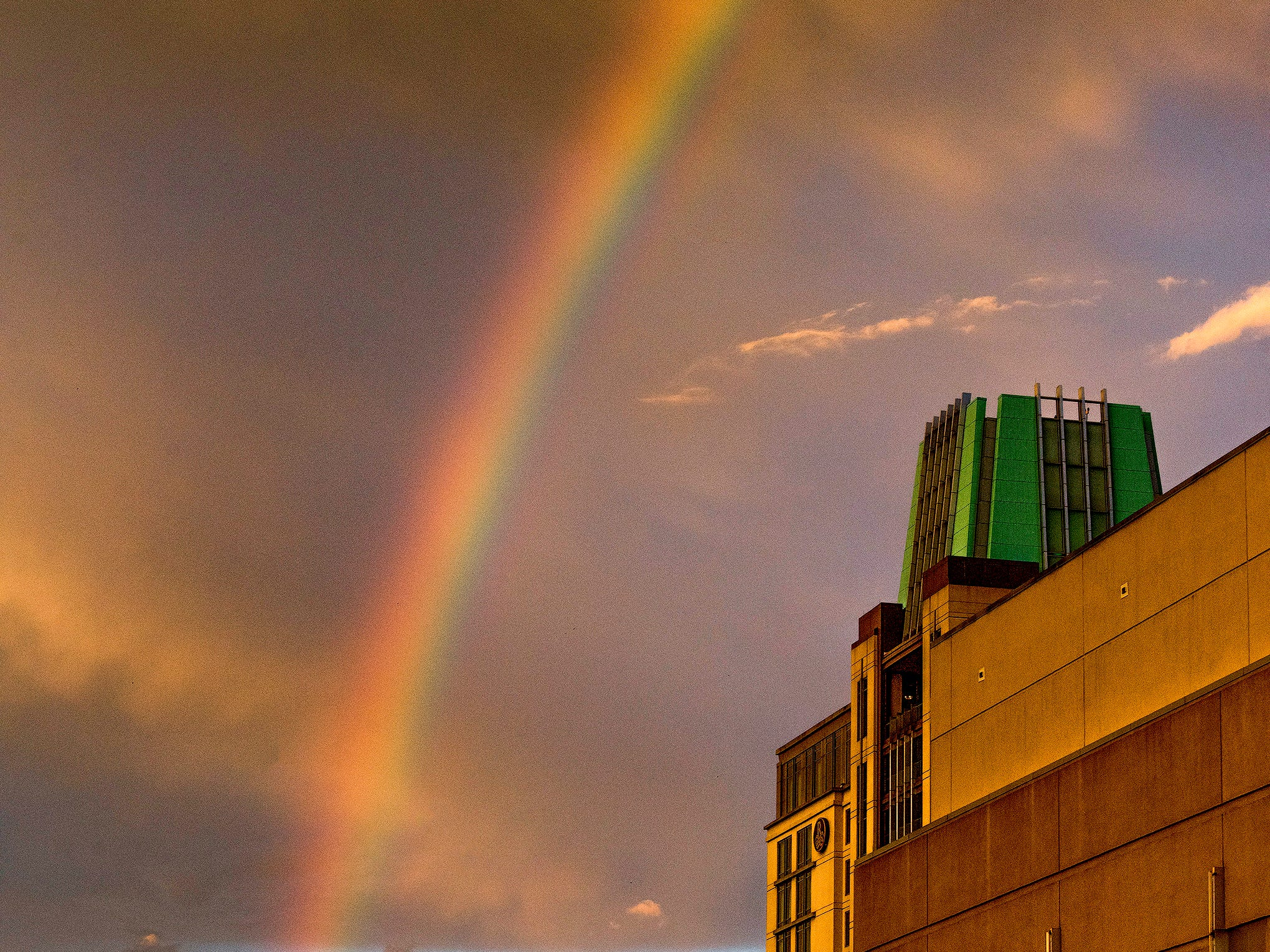 A rainbow is seen over Commerce Street in Montgomery, Ala., as the sun goes down on Tuesday August 28, 2018.