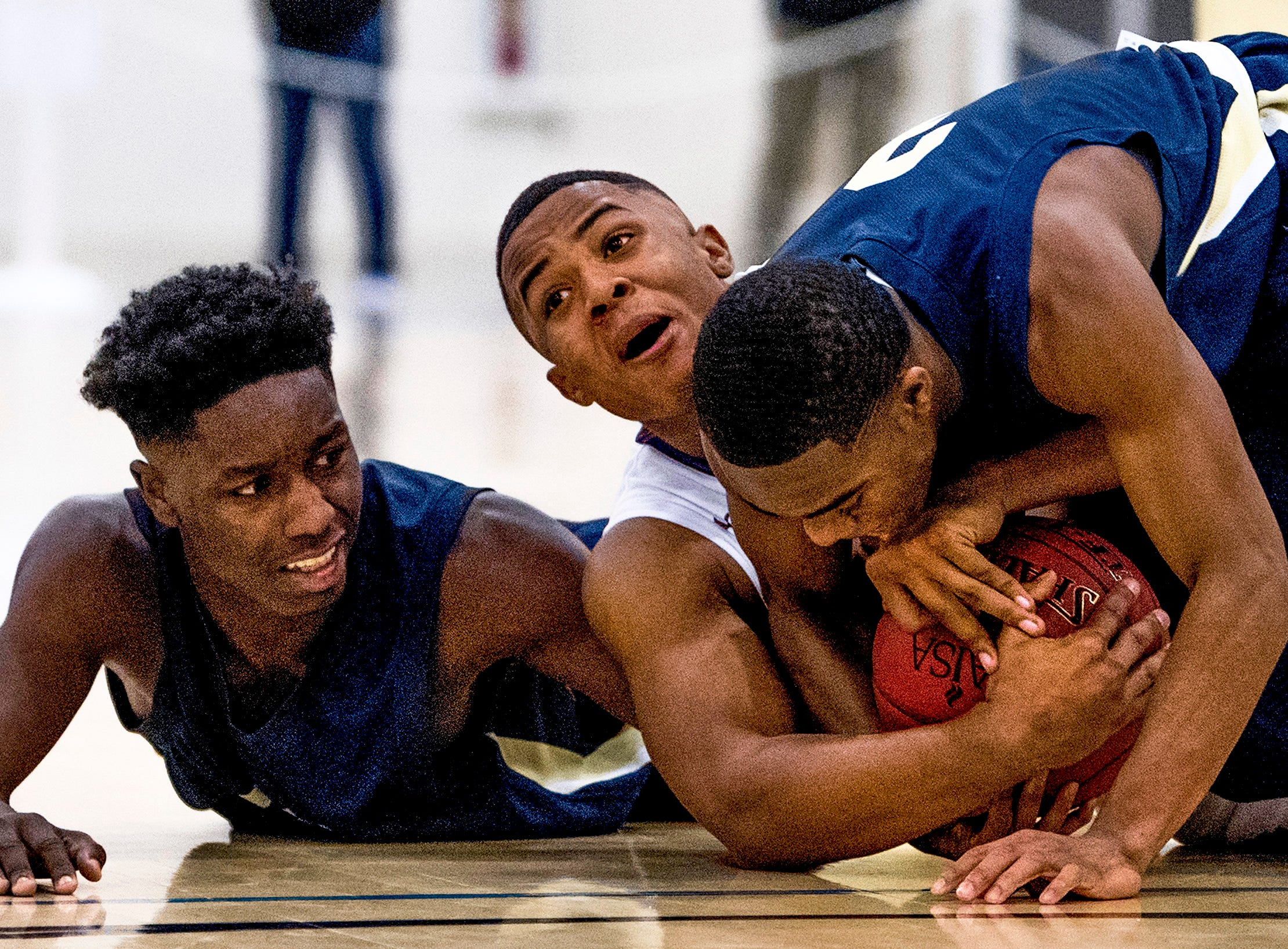 Evangel's Daryl Stewart, center, and East Memorial's A.J. Howard, left, and Lee Crawford, right, scrap for the ball in the AISA Class A Boys State Championship game in Montgomery, Ala., on Saturday February 3, 2018.
