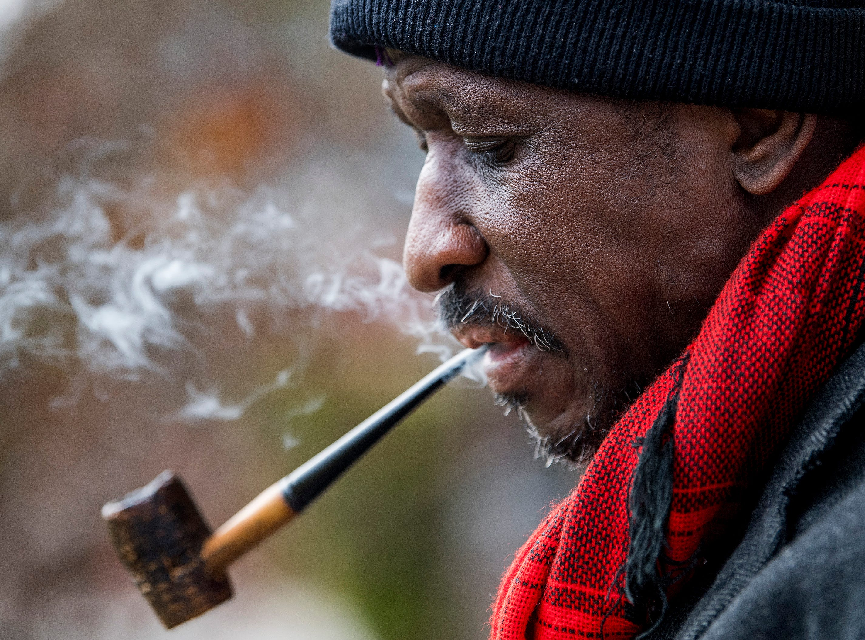 Bishop D.L. Muhammad smokes his pipe as he waits for his grandchildren to get out of school so he can walk them home on Tuesday afternoon February 15, 2018.