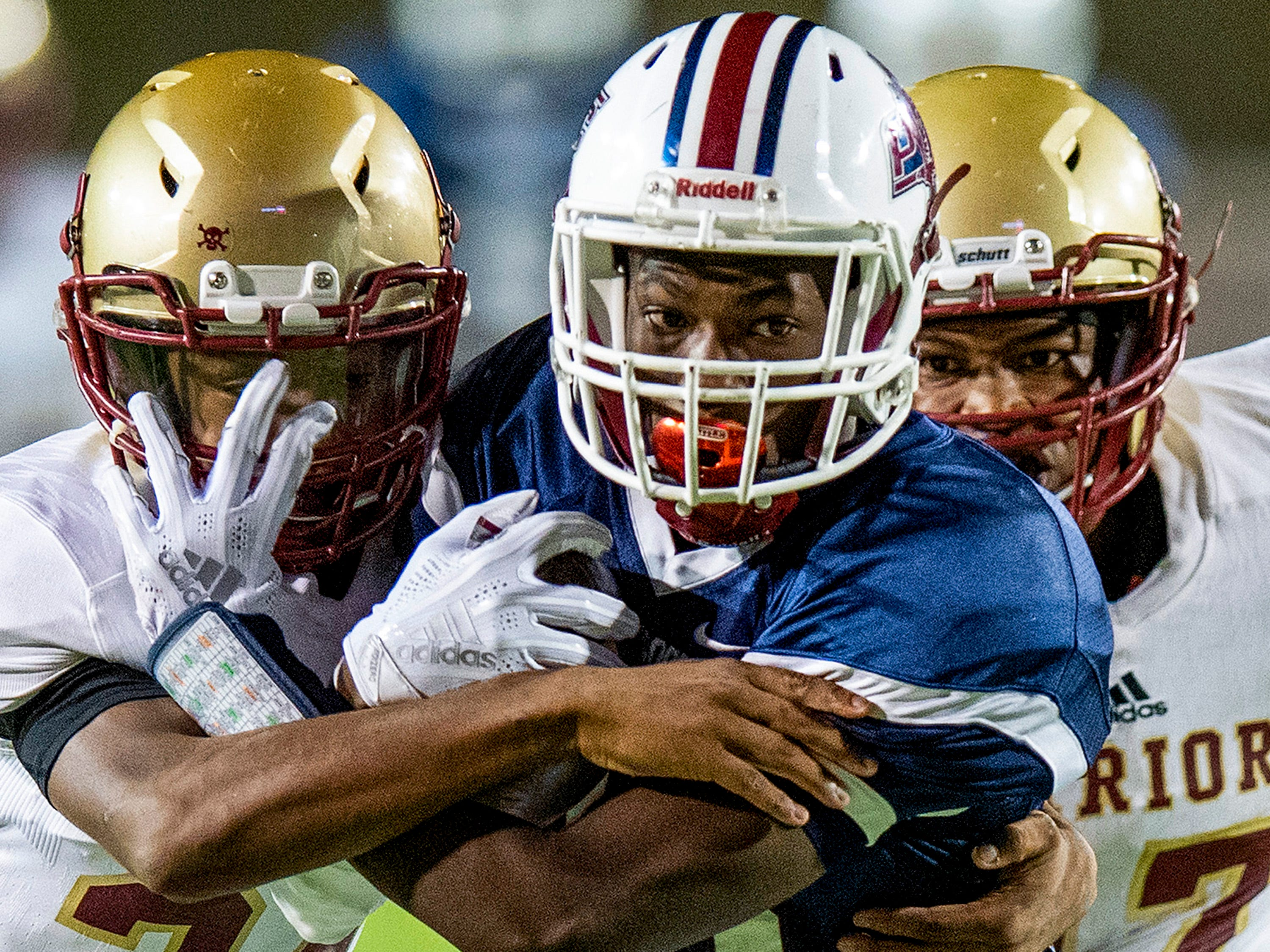 Park Crossing's Tacarius Buford (13) is stopped by Russell County's Keyshawn Reynolds (24) and Kelton Marshall (27) at Cramton Bowl in Montgomery, Ala., on Thursday October 18, 2018.