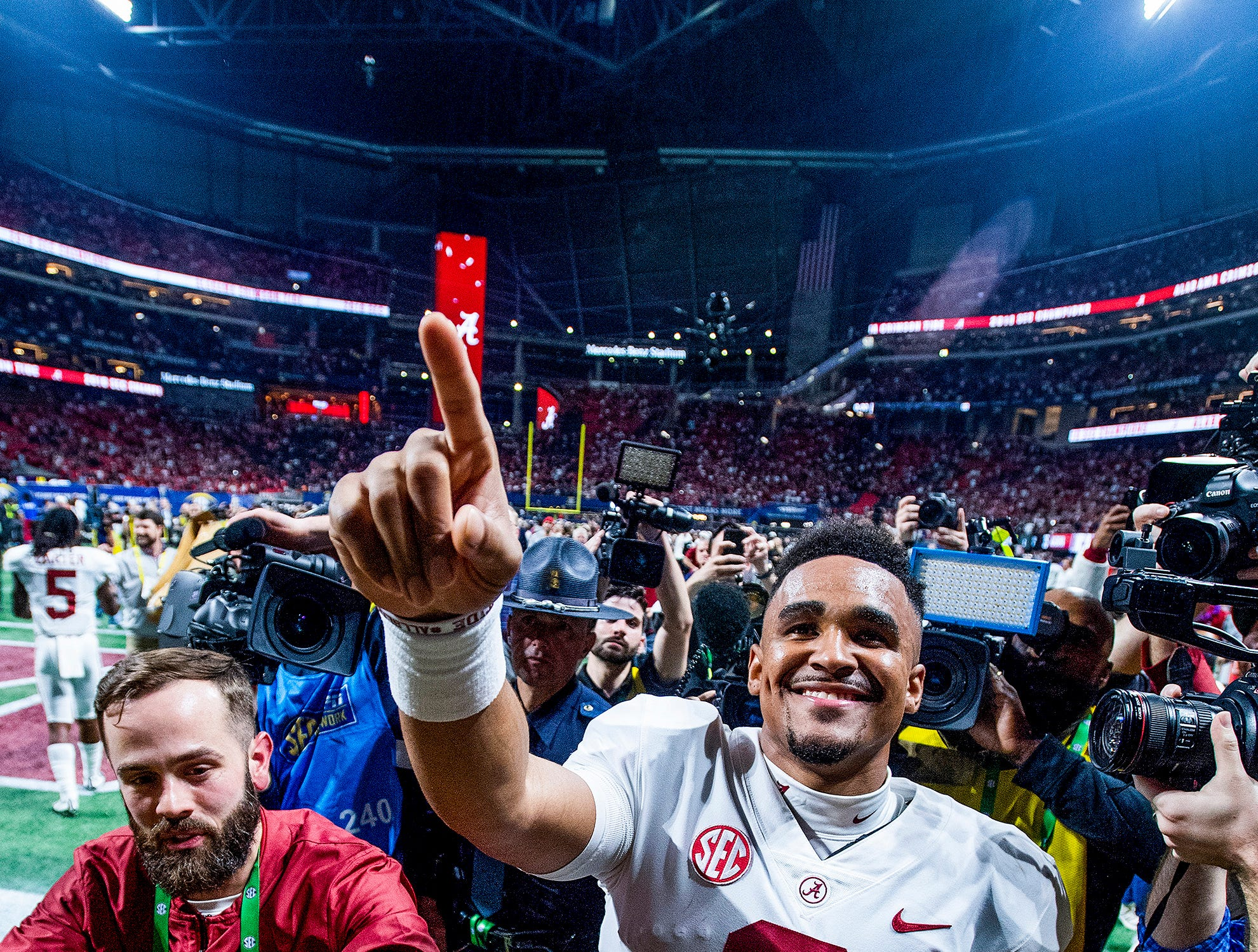 Alabama quarterback Jalen Hurts (2) signals number one as he waves to his family after defeating Georgia in the SEC Championship Game at Mercedes Benz Stadium in Atlanta, Ga., on Saturday December 1, 2018.