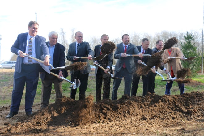 Elected leaders and Tennessee Department of Transportation officials throw dirt on the site of the new Mack Hatcher Memorial Parkway extension.