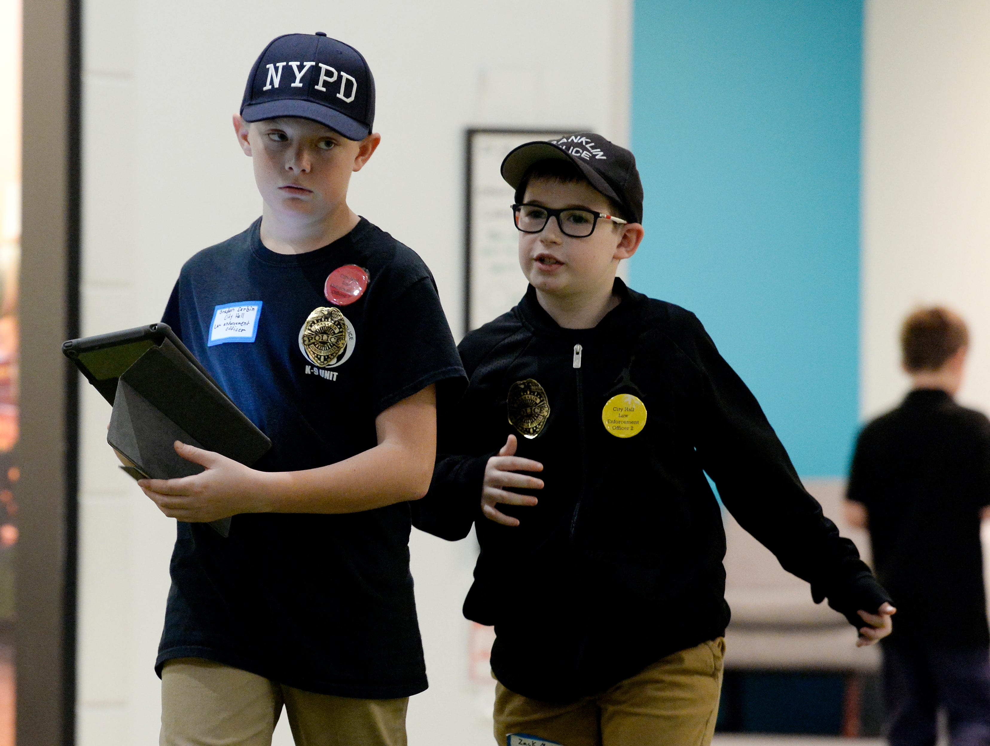 Student police officers Braden Serbin, left, and Zack Martin, look for violations in Junior Achievement's BizTown on Thursday, Dec. 13, 2018, in Nashville, Tenn. Mill Creek Elementary students participated in the program for fifth graders to learn how the economy works. Junior Achievement is expanding to add Finance Park in 2020 so students can learn about expenses and managing money.