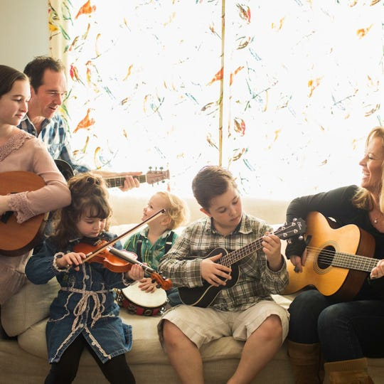 Stacy Jagger, right, plays music with her husband and four children. A child and family therapist in Nashville, Jagger helps families reconnect with her 30-day blackout program, which eliminates technology usage for a month. Playing instruments together is a family activity she recommends in place of technology.