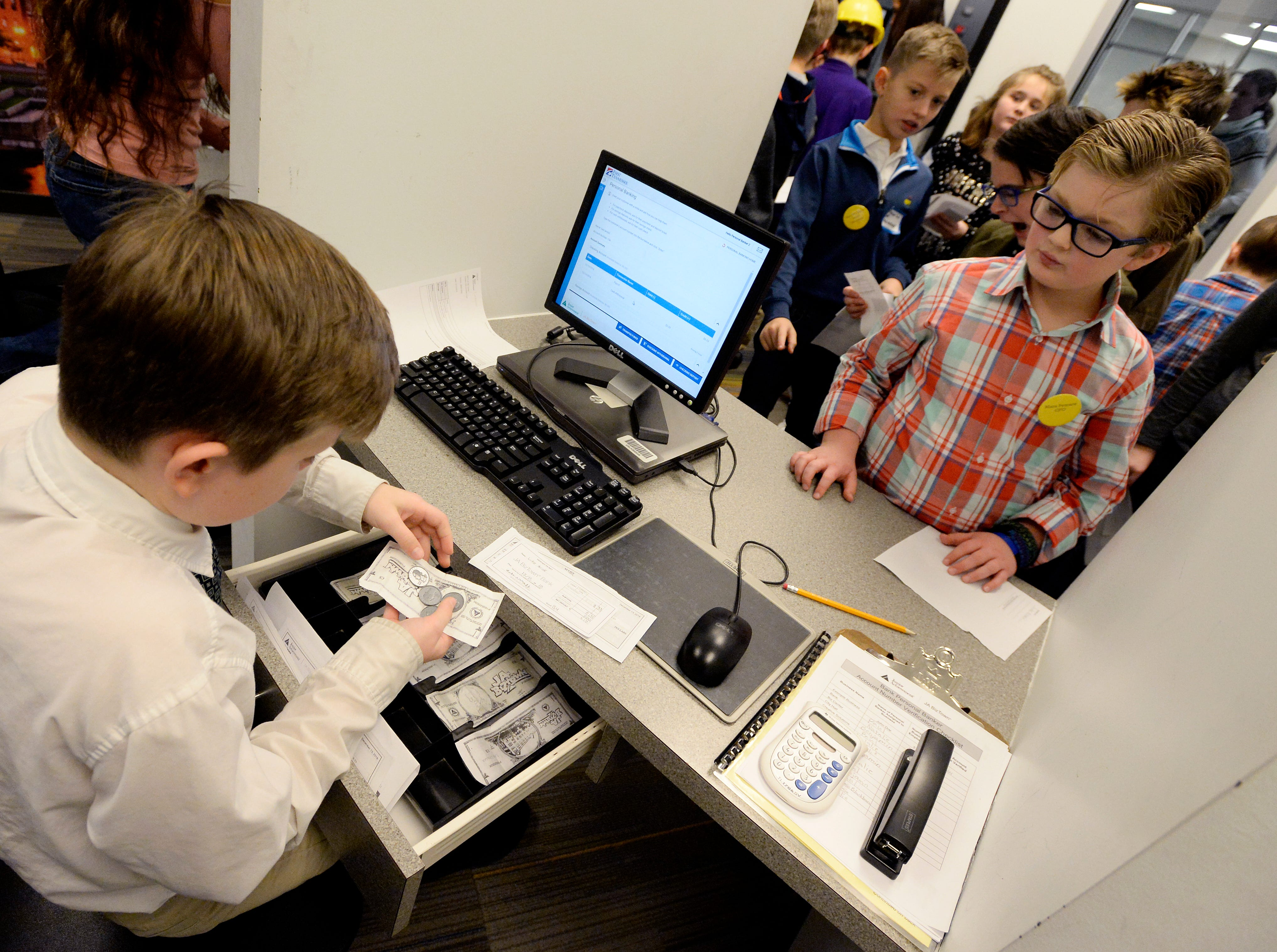 Mill Creek Elementary fifth-graders are paid by the student bank while attending the Junior Achievement BizTown on Thursday, Dec. 13, 2018, in Nashville. Students participate in the program to learn how the economy works.