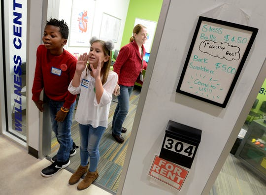 Chas Smith, the assigned Wellness Center CEO, left, and Blakley Loy, an assigned Wellness Center nutritionist, call for customers in Junior Achievement's BizTown on Thursday, Dec. 13, 2018, in Nashville. Mill Creek Elementary students participated in the program for fifth-graders to learn how the economy works.