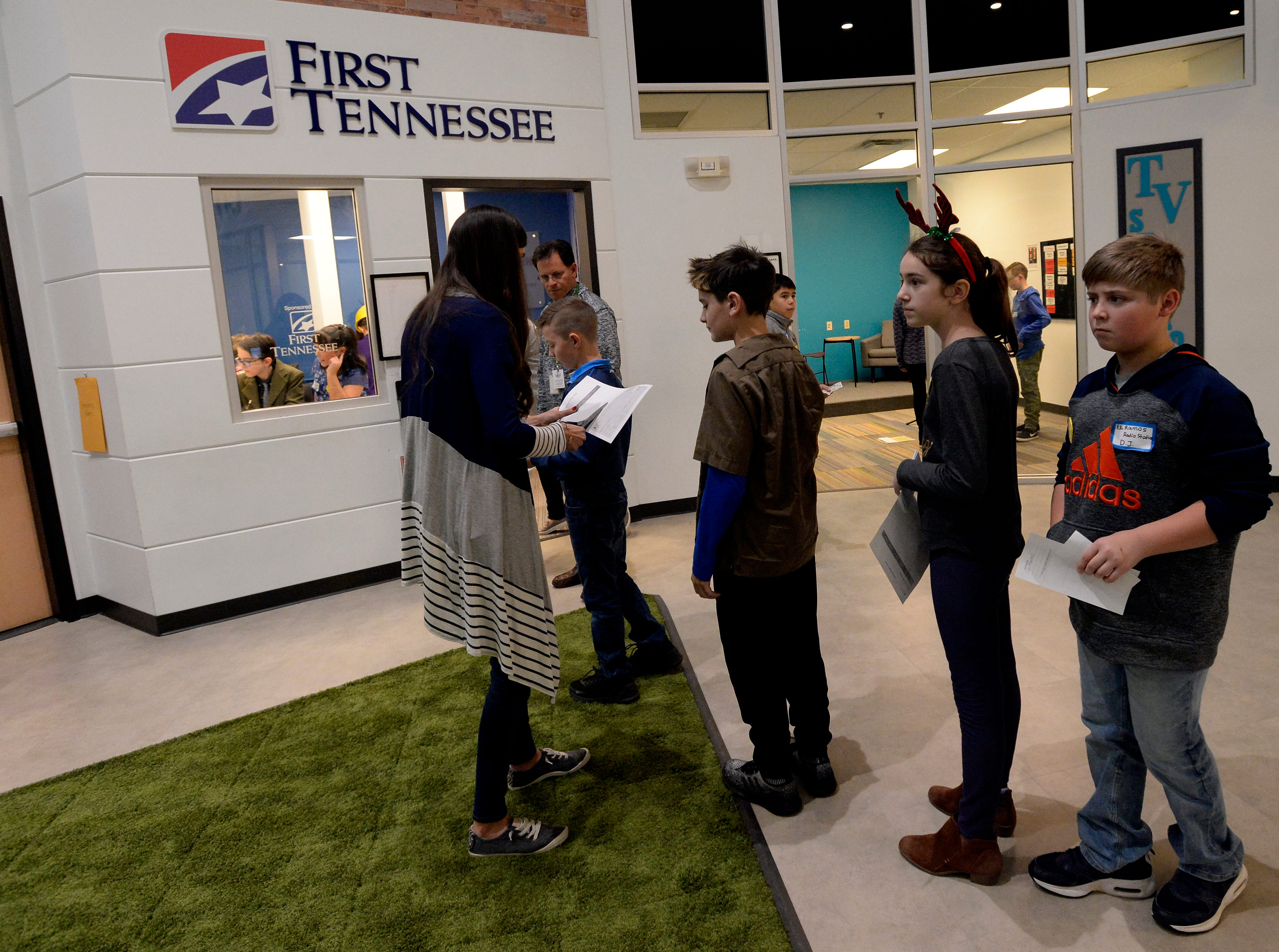 Mill Creek Elementary students wait to cash their checks while attending the Junior Achievement BizTown, Thursday, Dec. 13, 2018, in Nashville, Tenn. The program for fifth graders helps students learn how the economy works. Junior Achievement is expanding to add Finance Park in 2020 so students can learn about expenses and managing money.