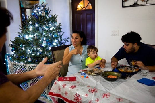 Yudeisy Cala, center, laughs as she talks to Alodia Rodriguez, left, while Delvis Pardo, right, entertains Renzo Sander Lorenzo, 1, during dinner on Friday, Dec. 14, 2018, in East Naples.