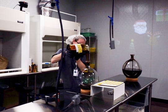Sam Tomlinson pours thick crude cannabis oil into a container at the Trulieve manufacturing facility in Gadsden County, Fla., in December 2018.