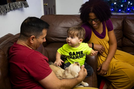 Luis Lorenzo, left, and Aloima Cata, right, talk to their son Renzo Sander Lorenzo, 1, as he pets the family dog Rapunzel on Friday, Dec. 14, 2018, at their home in East Naples.