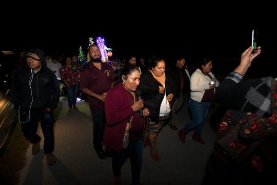 Miembros de la comunidad rezan mientras caminan en una procesión en Breezewood Drive en Immokalee durante la primera noche de Las Posadas el domingo 16 de diciembre de 2018.