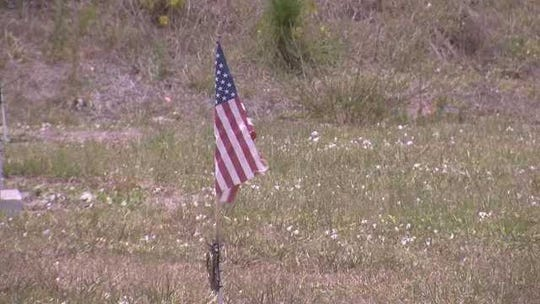 A flag is planted in the veterans' section of Lake Trafford Memorial Gardens in Immokalee at the start of the cemetery's restoration project in 2012.